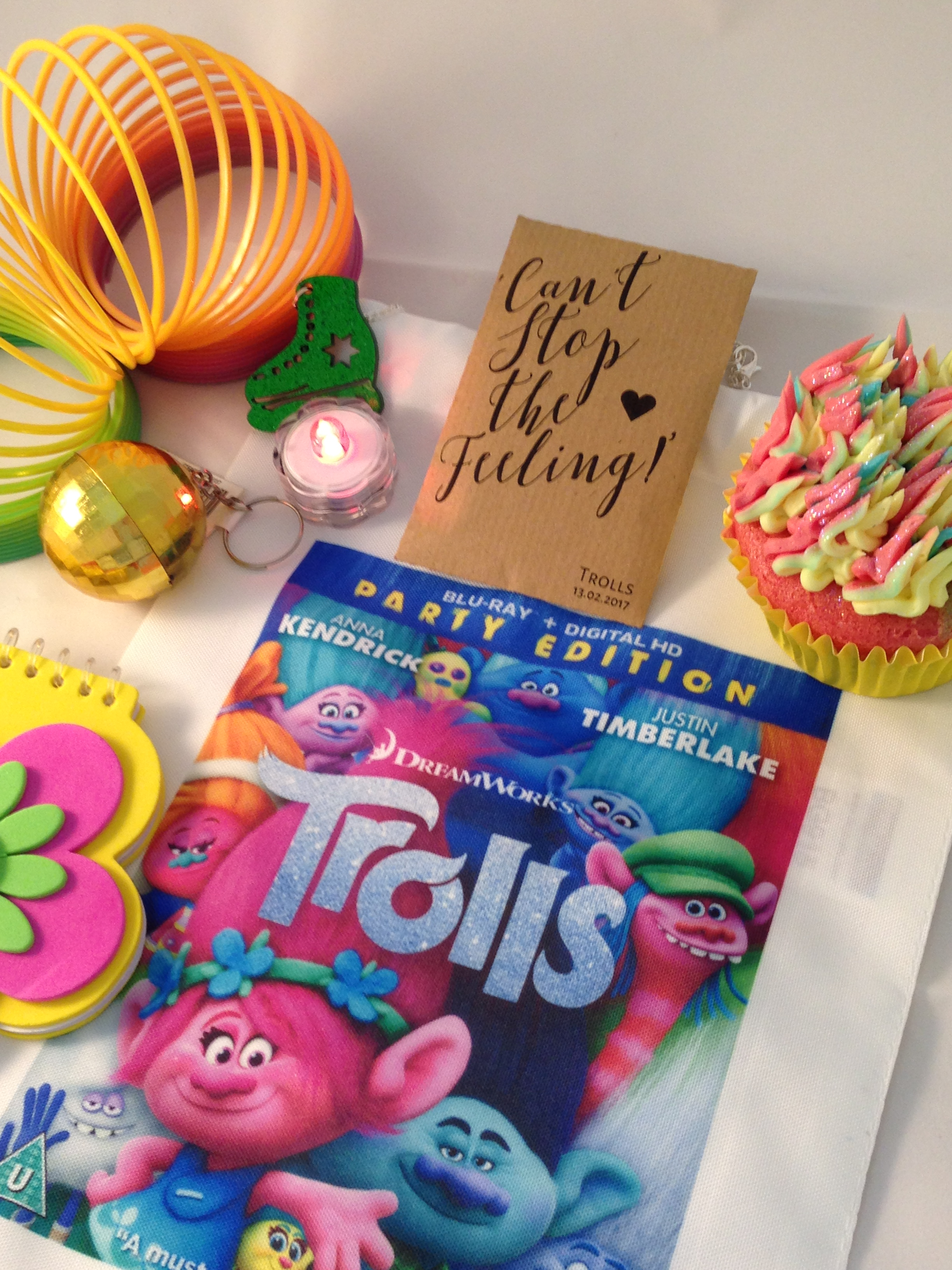 A spread of toys and trinkets given to children in a goodie bag at a screening of TROLLS at the Prince Charles cinema. There is a Trolls programme booklet, a colourful flower notepad, a slinky, a mini glitterball, a packet of seeds, and a glitter cupcake.