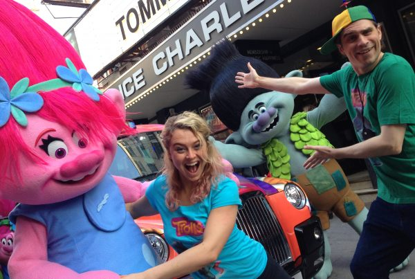 Two lively performers present two big colourful characters from the movie Trolls outside the front of the Prince Charles Cinema
