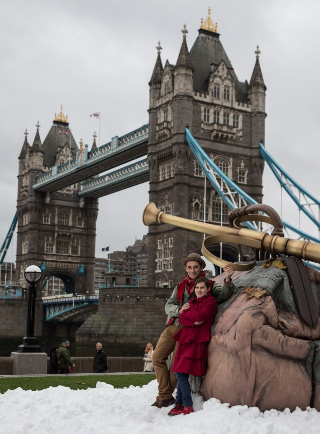 Stars Ruby Barnhill and Mark Rylance stood in front of a giant bag and dream trumpet in the snow, in front of Tower Bridge, London.