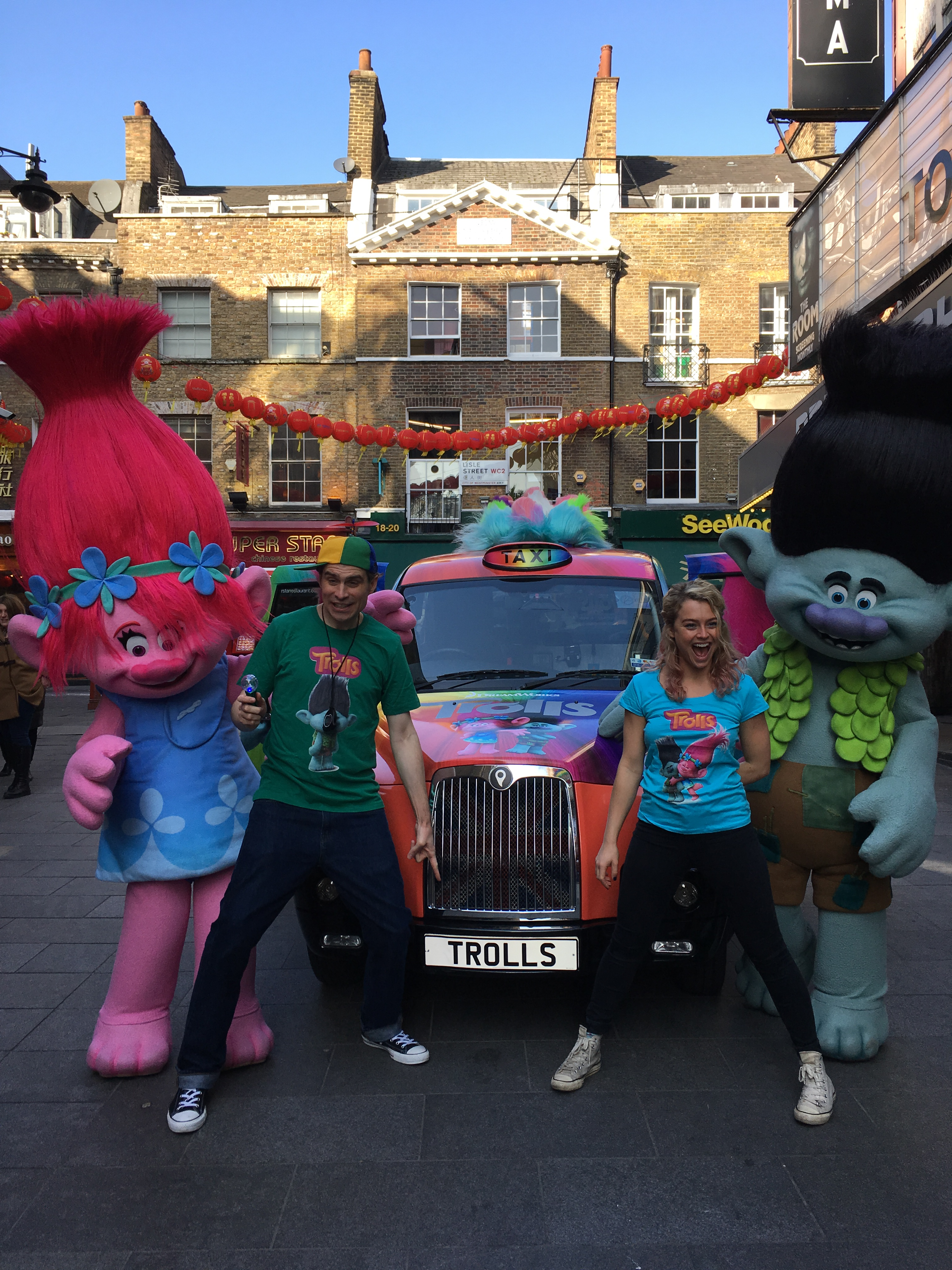 Two enthusastic brightly dressed presenters stand next to two large colourful costume characters from the movie TROLLS, infront of a branded London Taxi cab. The cab is rainbow coloured, and has Trolls branding on it, and the number plate 'TROLLS'.