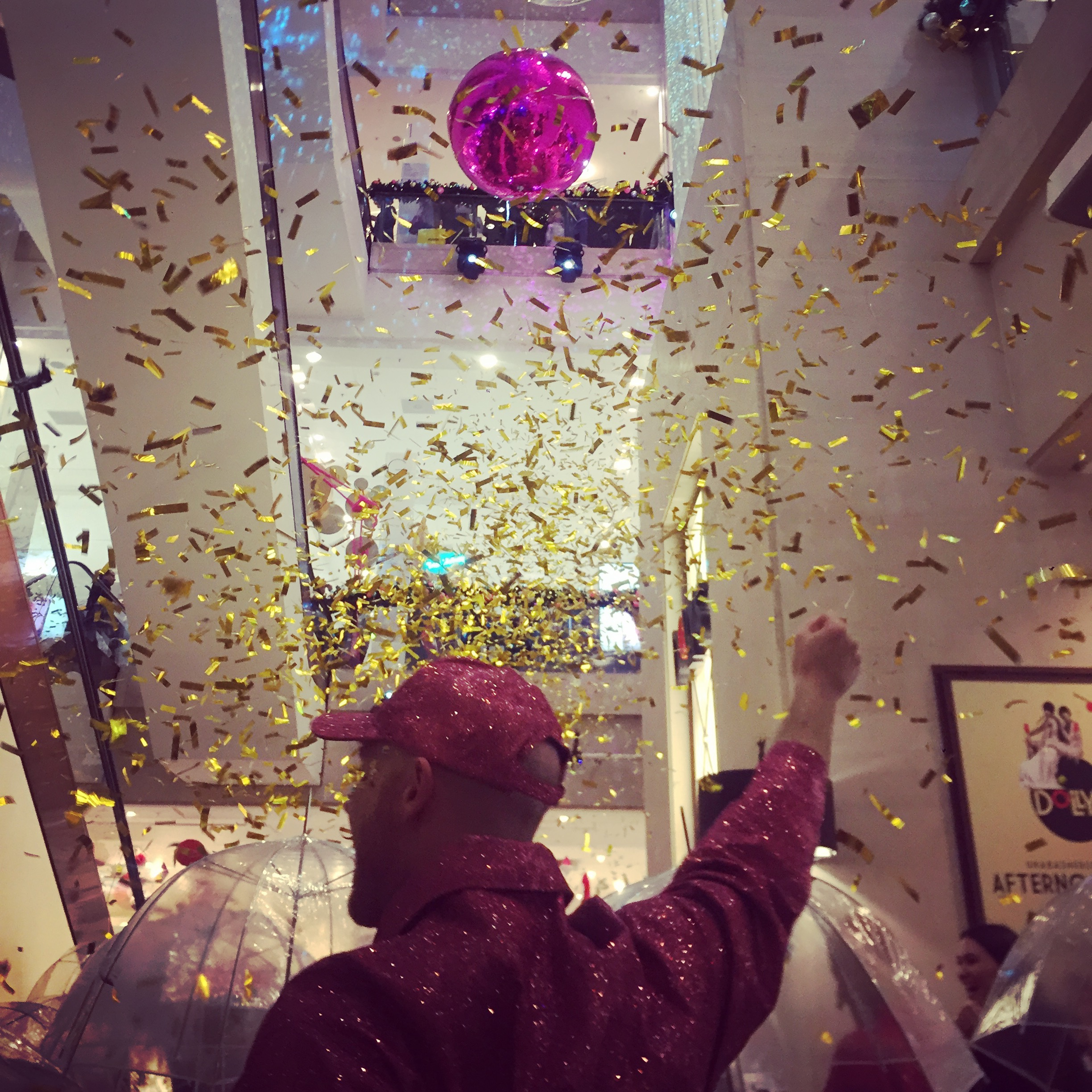 Glitter confetti falls around a male disco dancer wearing a pink sequin costume entertain guests at Selfridges Christmas Entertainment