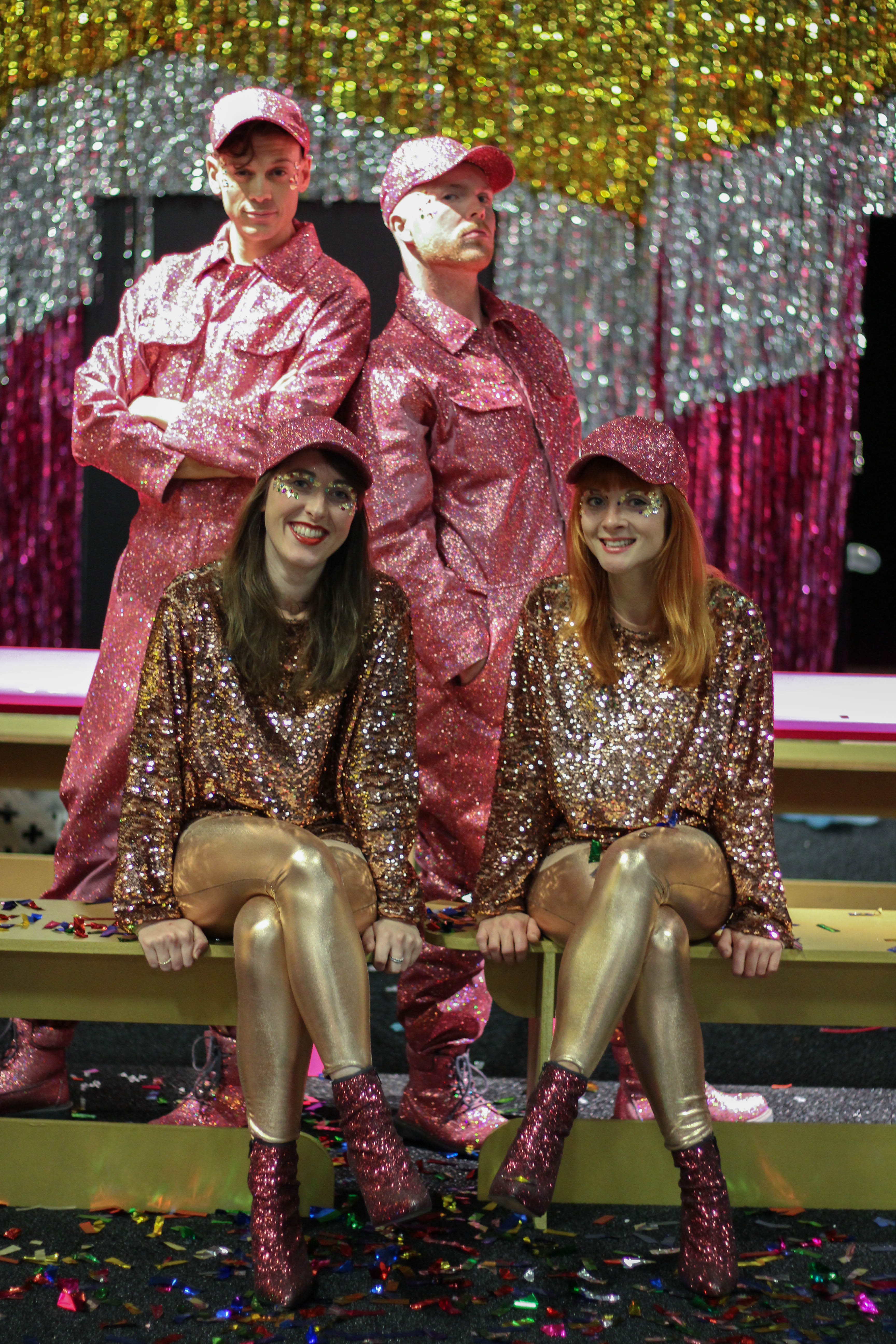 A dance troupe consisting of 2 girls and two boys sitting on a bench wearing gold and pink sequin costumes with glitter flocked baseball caps pose for photos for Selfridges Christmas Entertainment