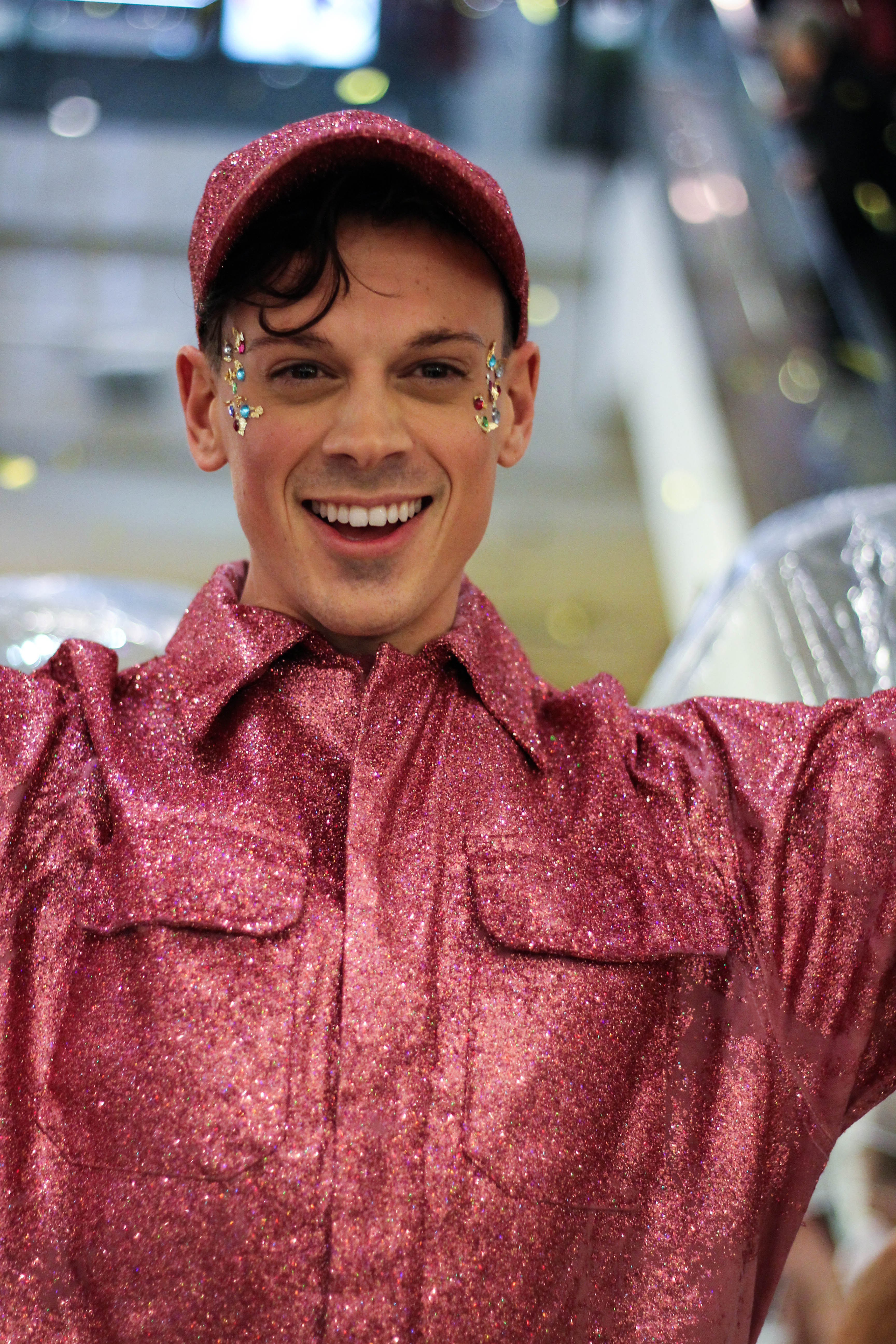 A male disco dancer wearing a pink sequin costume entertain guests for Selfridges Christmas Entertainment