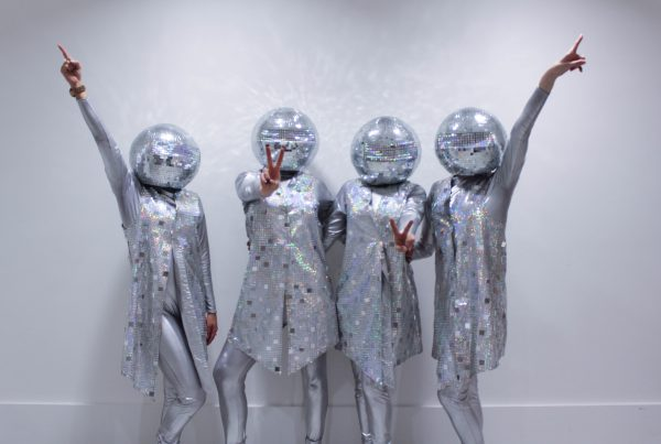 Four glamorous dancers wearing bespoke silver sequin costumes with glitter ball helmets pose during their dance routine for Selfridges Christmas Entertainment