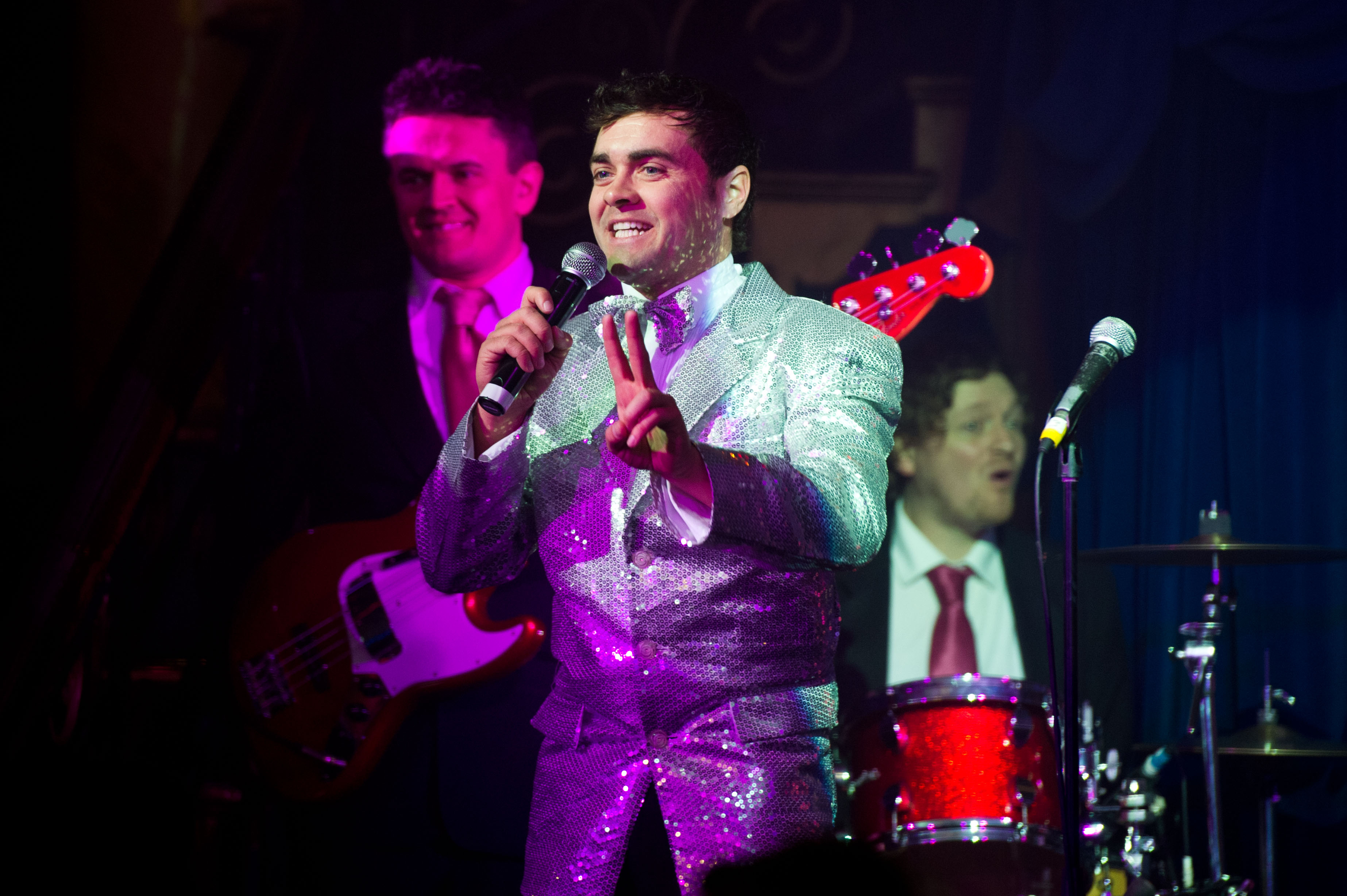 A smiling host in a sparkly silver jacket talks into a microphone with a guitarist and drummer behind him.