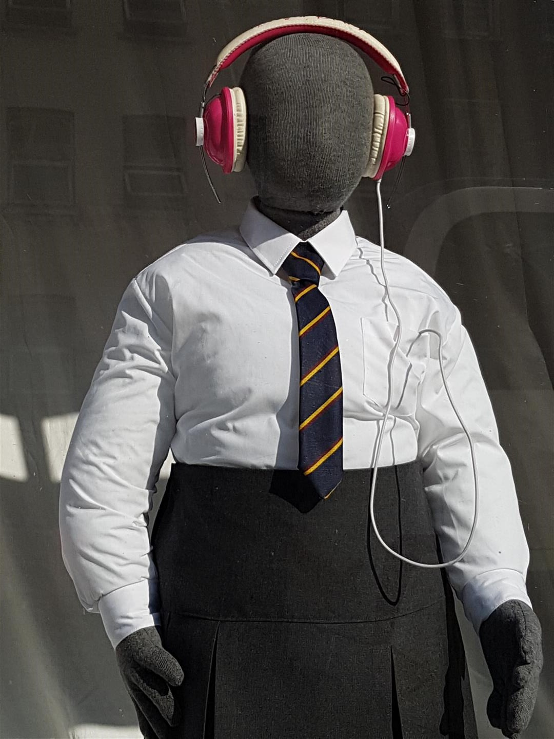 An obese mannequin in tight girls school uniform and pink headphones in a window display.