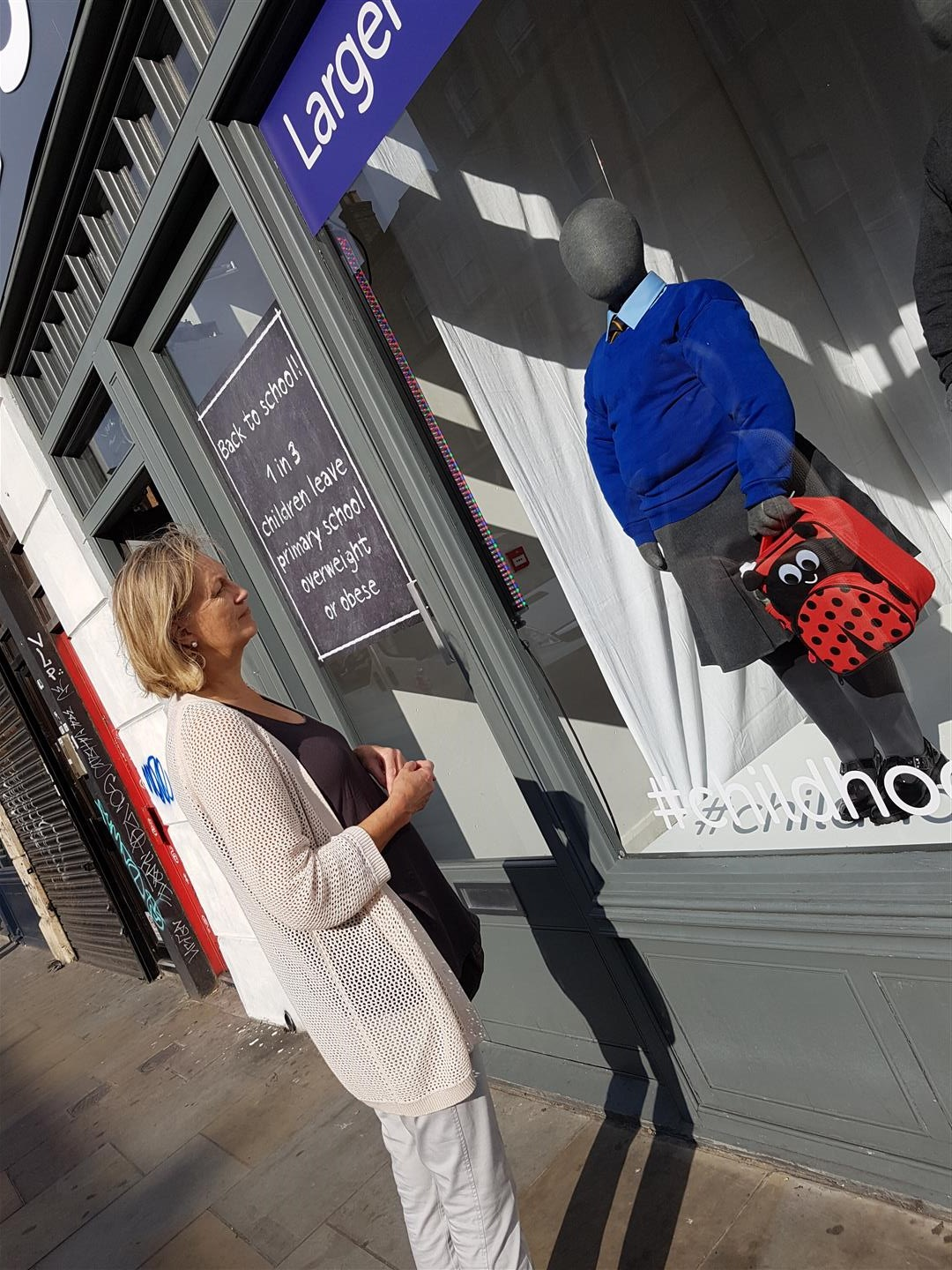 A lady passing by examines a window display containing obese mannequins in tight school uniforms.