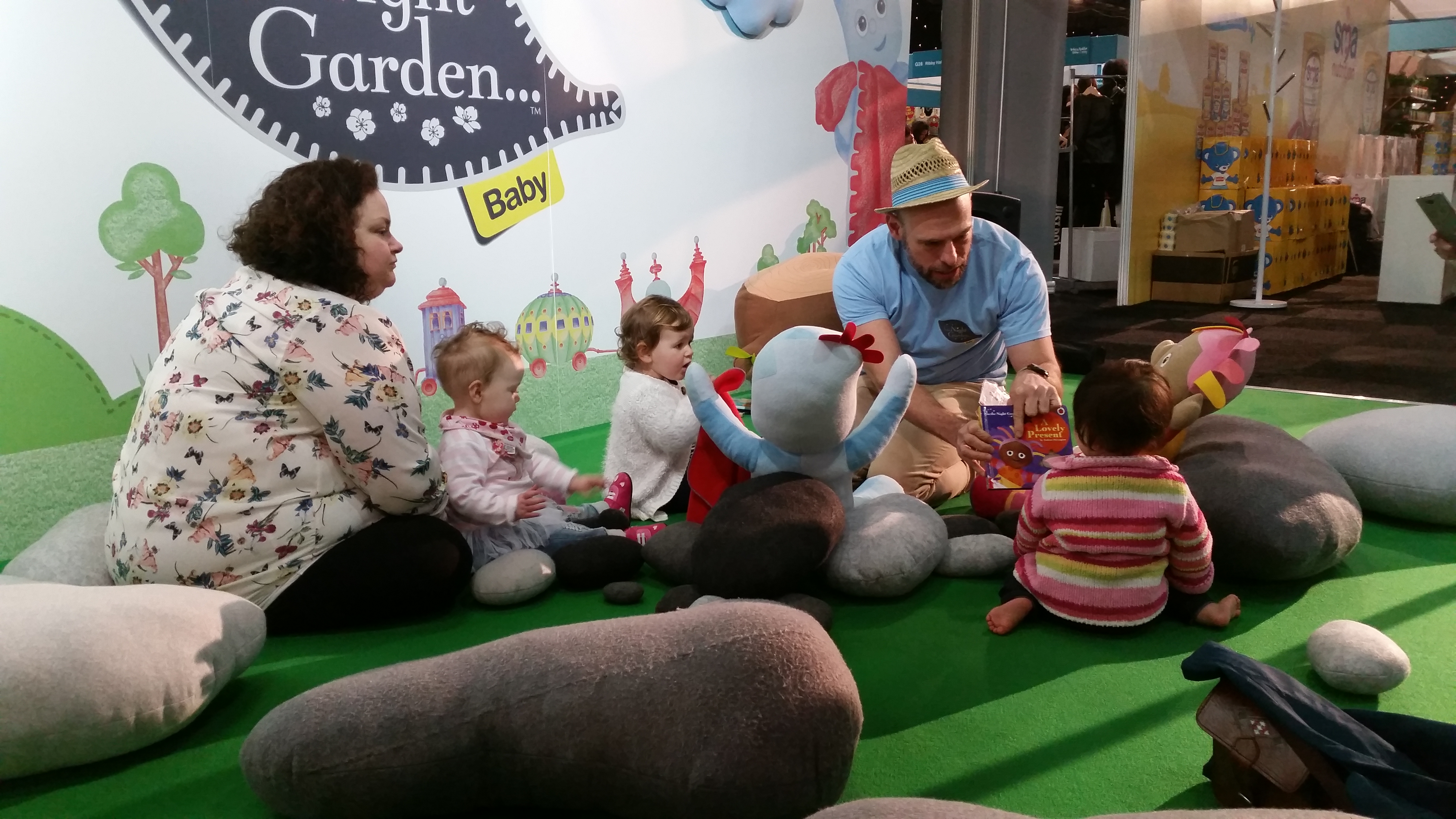 A grpoup of toddlers and parents sit gathered round a storyteller in a comfy In The Night Garden stand