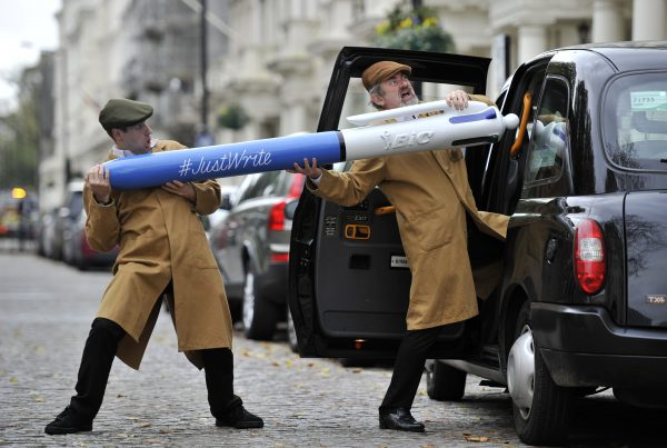 Two performers dressed as delivery men in flatcaps and overalls carrying a giant BIC pen, climb into a black London taxi Cab.
