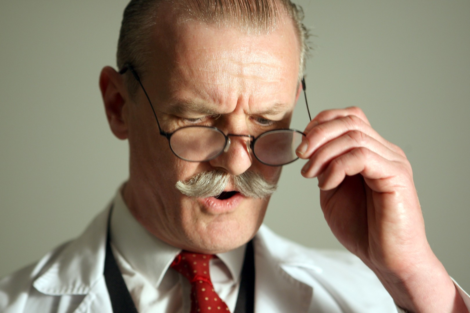 A mustachioed biologist in a white lab coat in the process of removing his spectacles
