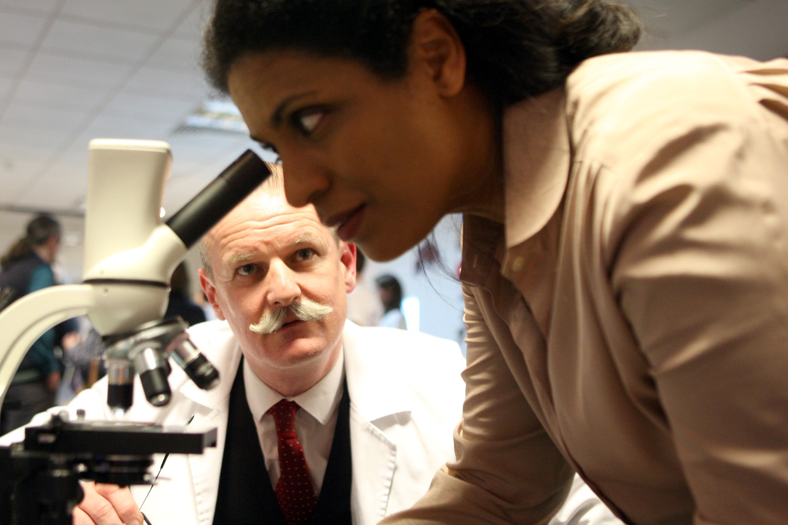 A woman looks into a microscope as a mustachioed biologist watches on.