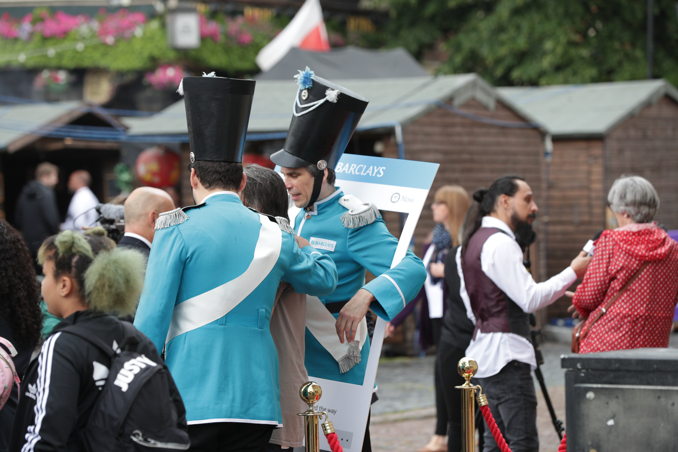 2 guards dressed in Barclays brand colour cyan entertain a woman attending the celebration of the world's first ATM