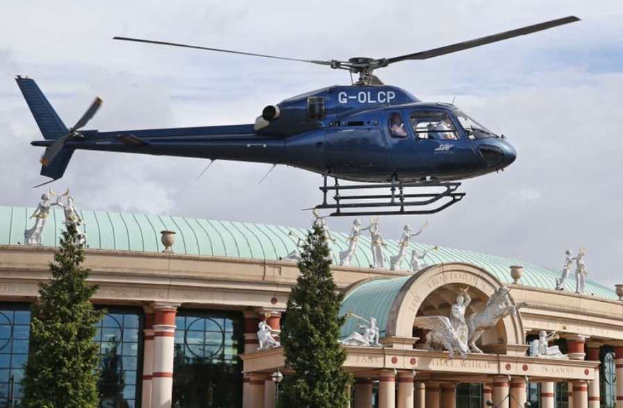 A navy blue helicopter hovers above the Trafford Centre in Manchester