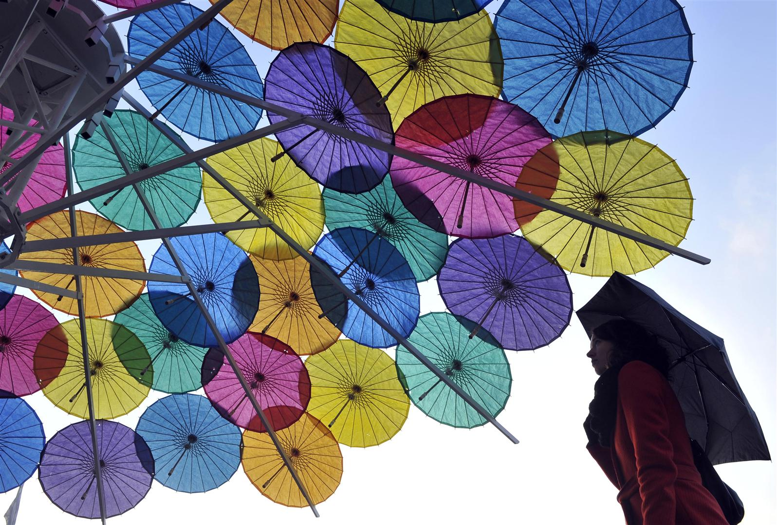 A lady in a red coat holds an umbrella, underneath a giant cocktail umbrella constructed lots of multi-coloured parasols.