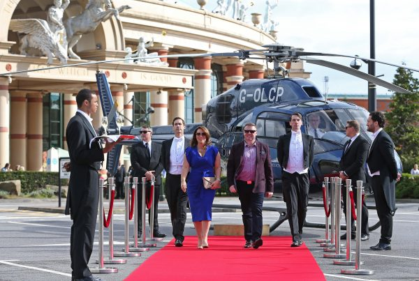 A smiling couple walk down a red carpet from a navy helicopter escorted by two very smart looking butlers in black and white suits whilst security guards in black suits and dark glasses watch on. ANother butler stands at the end of the red carpet holding a silver tray with 2 champagne glasses on it.