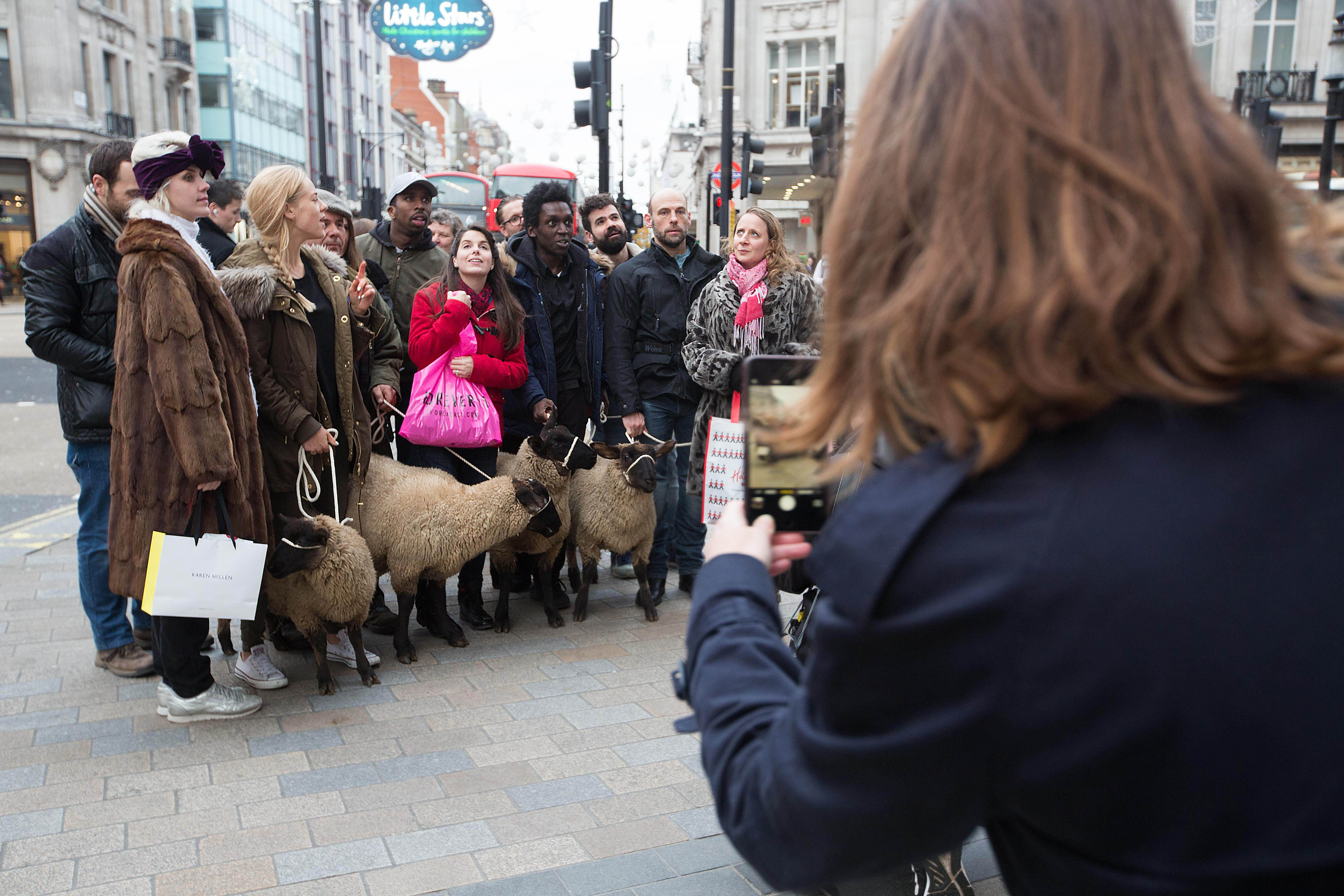 A lady in a dark blue overcoat captures a photograph on her phone of a group of people dressed as shoppers each holding a woolly sheep on a rope huddled together at London's Oxford Circus.