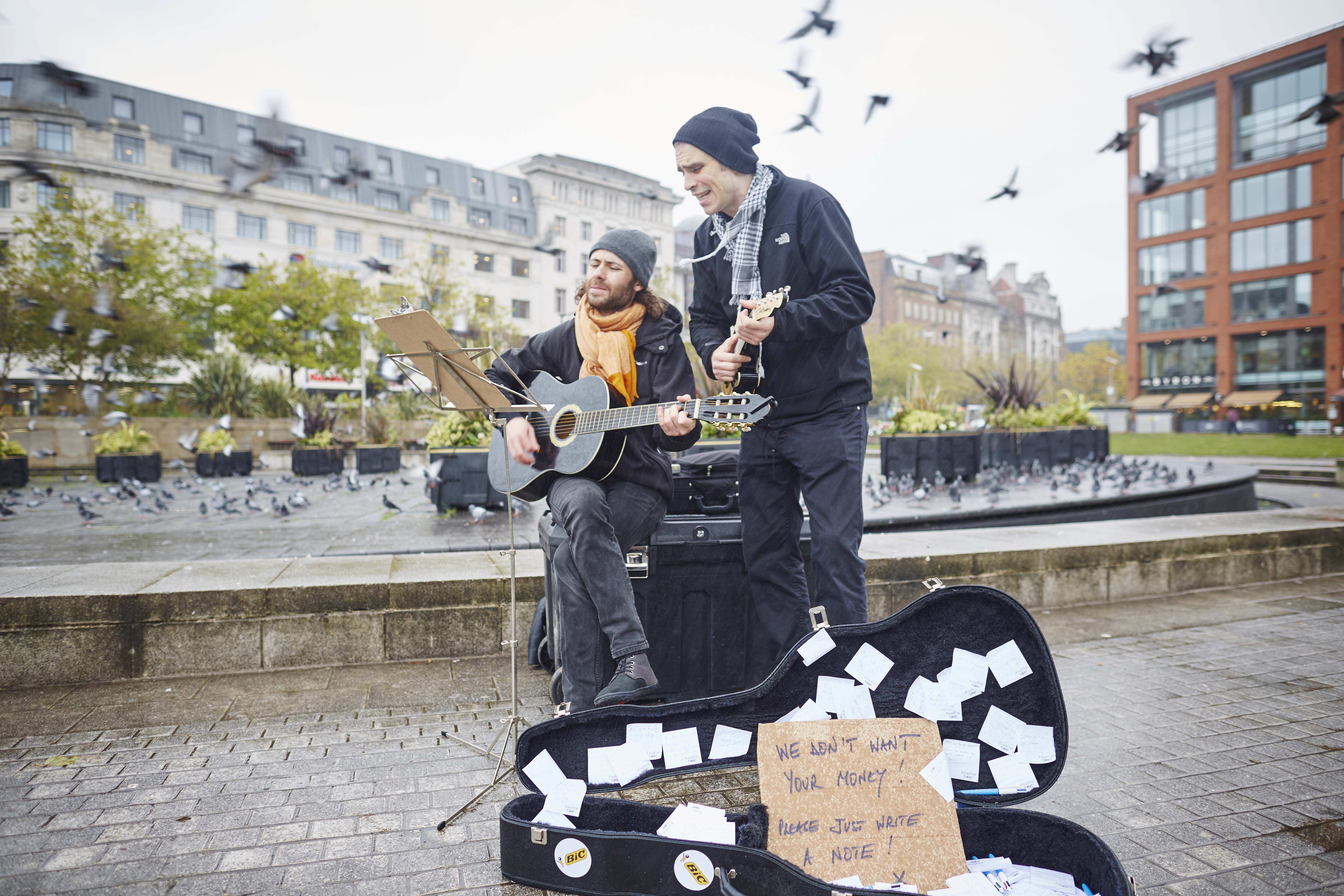 Two men dressed as buskers holding guitars play infront of an opened guitar case as pigeons scatter in the backgrpound