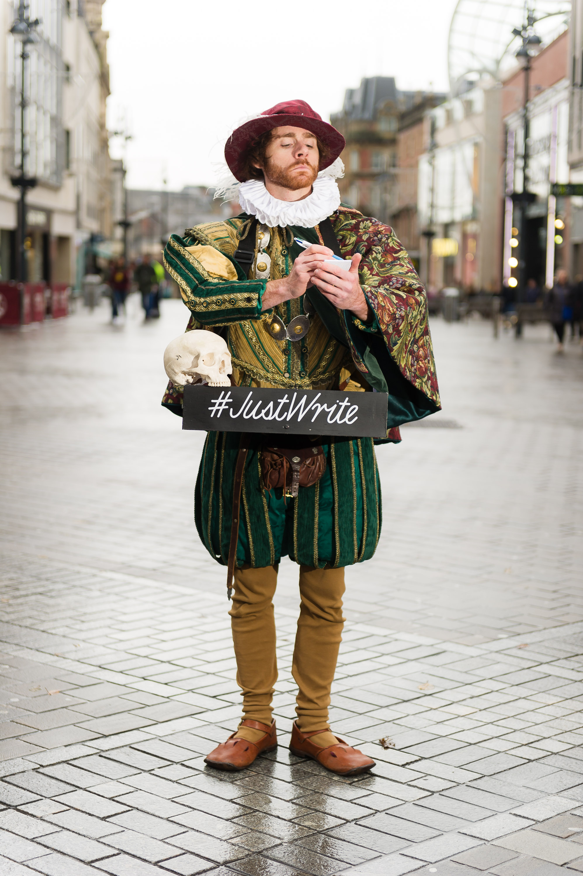 An actor dressed as William Shakespeare on a cobbled street.