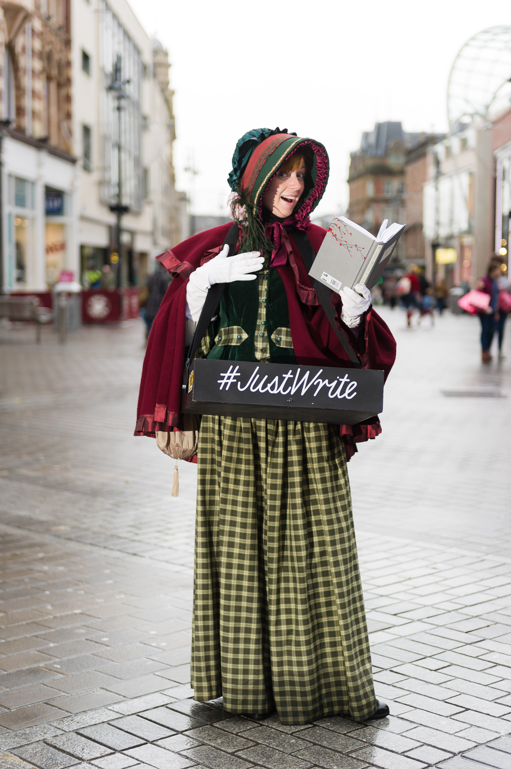 An actor dressed as Emily Bronte on a cobbled street.