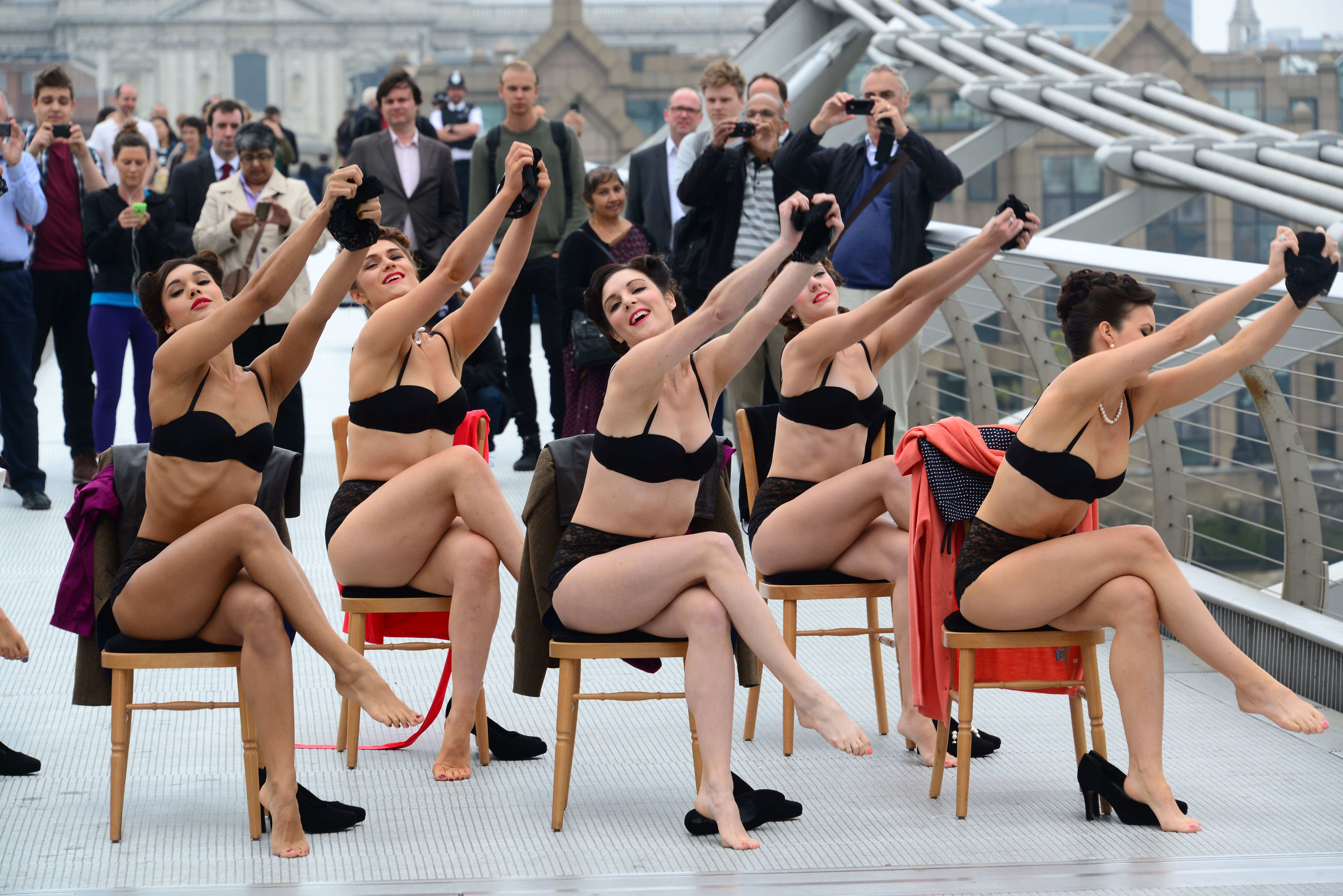 A group of dancers in underwear perform a choreagraphed reverse striptease on millennium bridge as members of the public watch on.