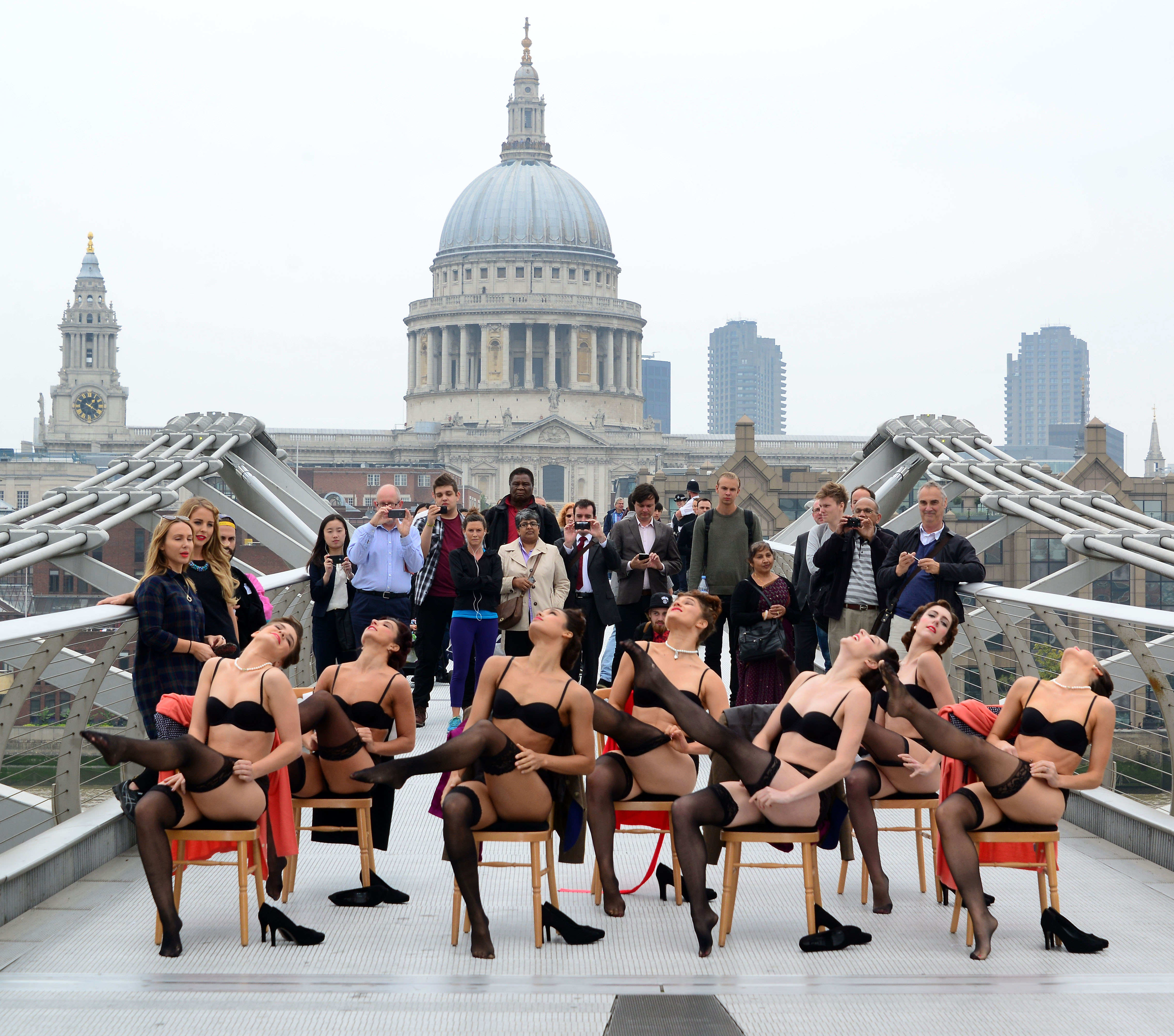 A group of dancers in underwear perform a choreographed dance routine on millennium bridge in the shadow of St Paul's cathedral.
