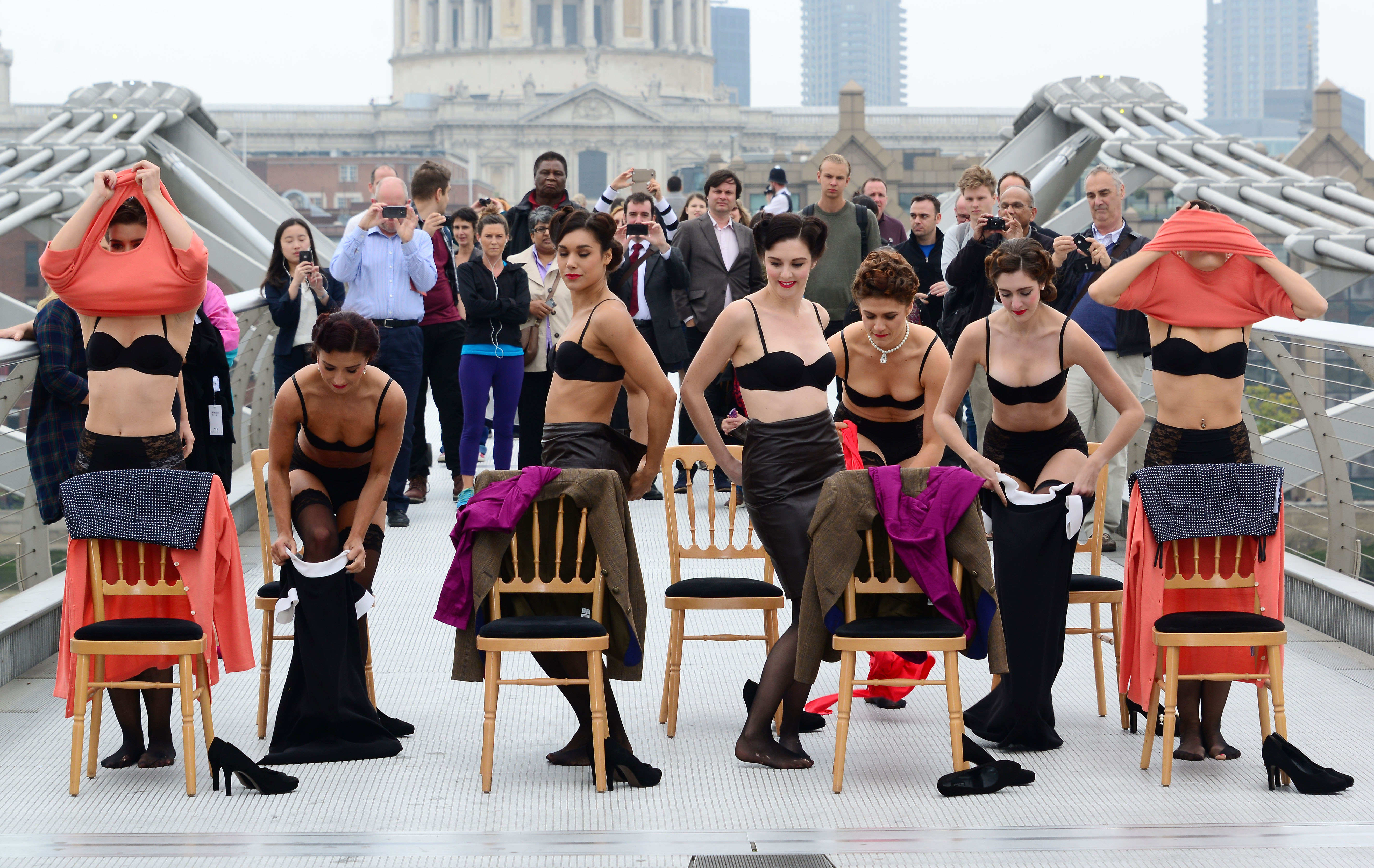 A group of dancers in the midst of a revers striptease putting clothes on Millennium bridge.
