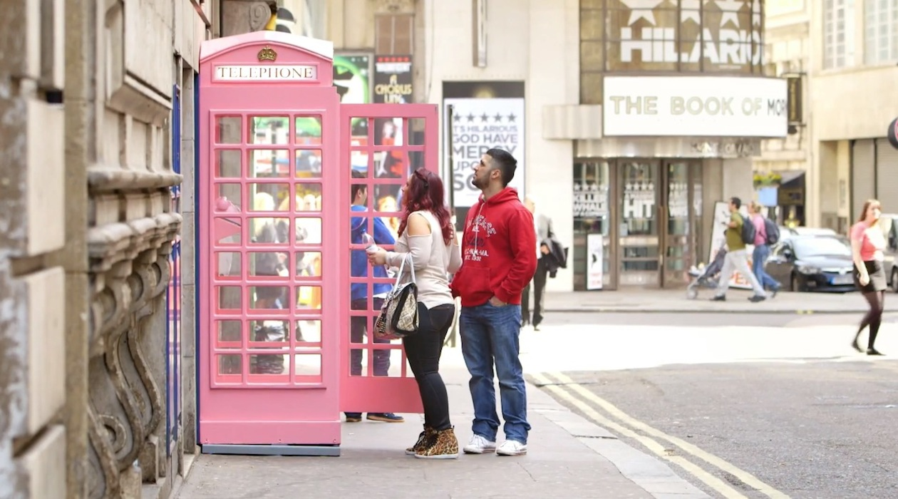 A bearded man in red hooded top, and a burgundy haired woman in white top open the door to a pink coloured London telephone box.