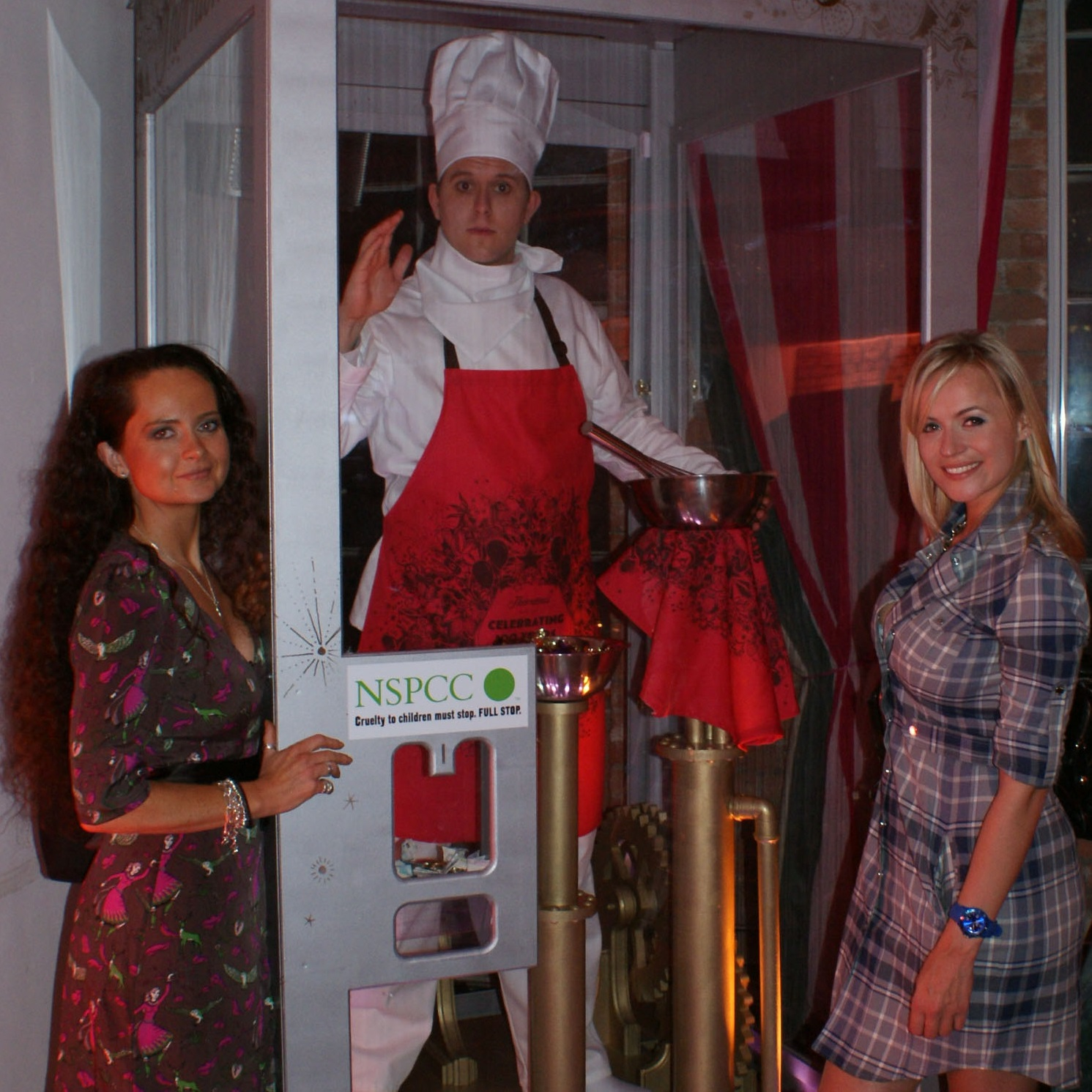two female guests stand either side of a performer dressed as a mechanical chocolatier in chefs clothing in a glass case