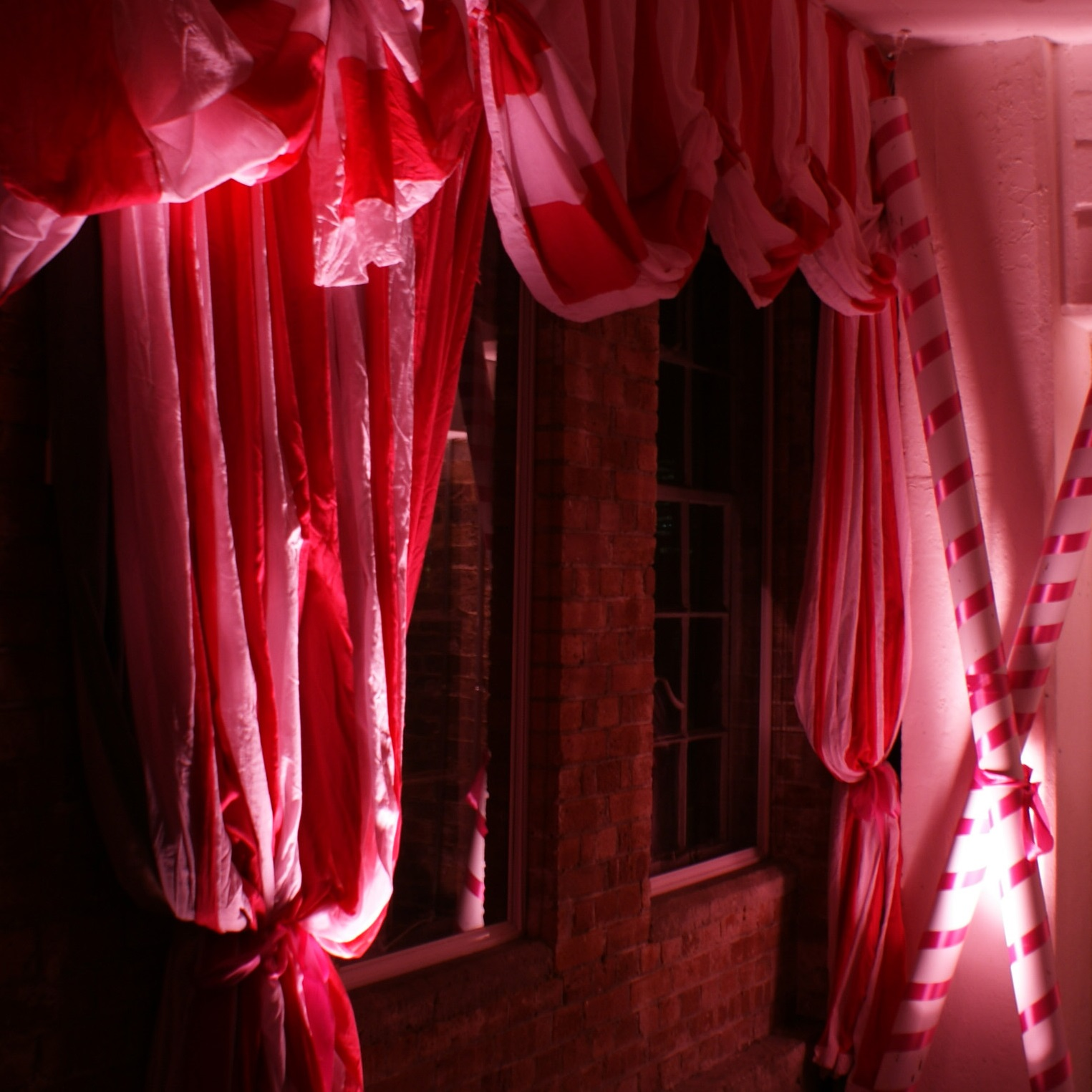 An illuminated pair of pink curtains and giant candy canes