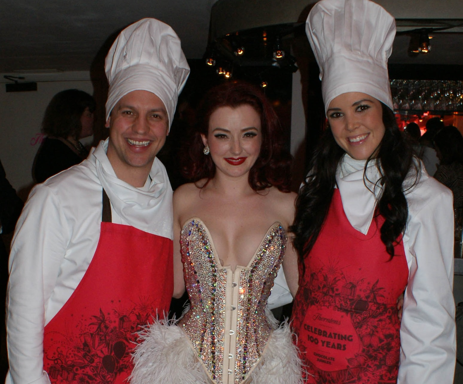 Two smiling chefs stand either side of a burlesque dancer