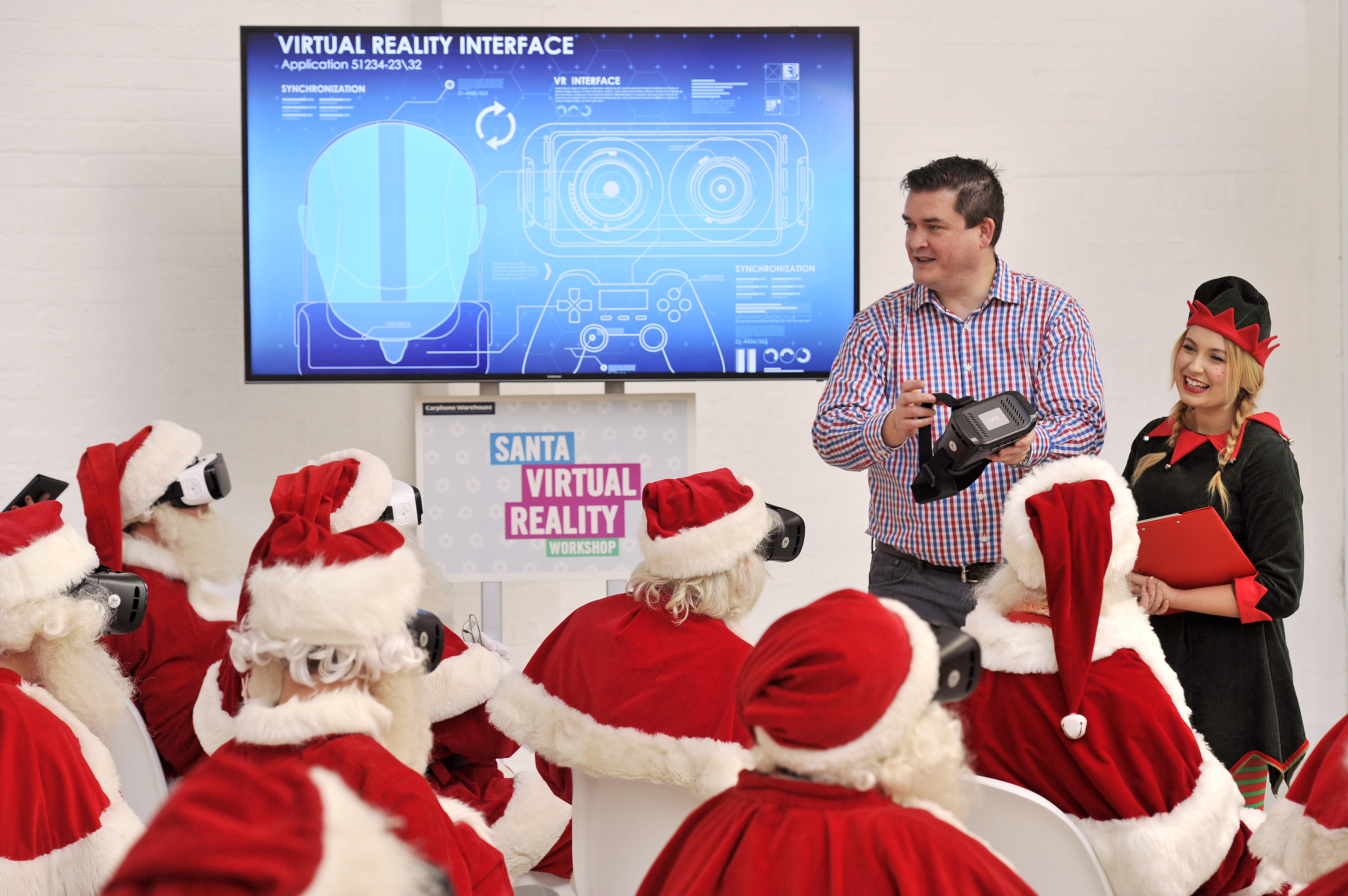A group of Father Christmases wearing virtual reality headsets sit listening to a presentation about VR technology by a man in a checked shirt and an elf helper.