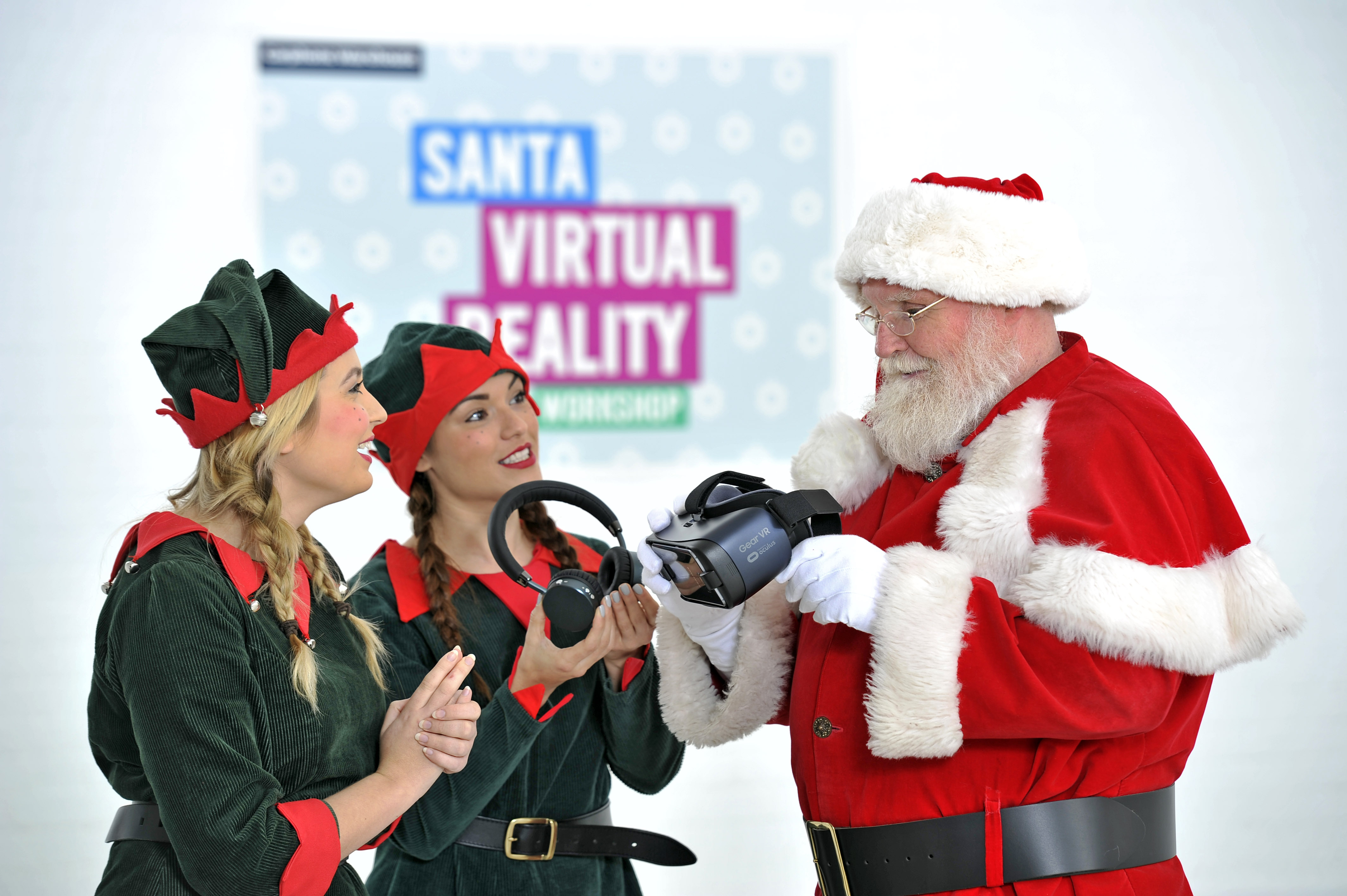A red-suited Father Christmas studies a virtual reality headset, guided by two elf helpers.