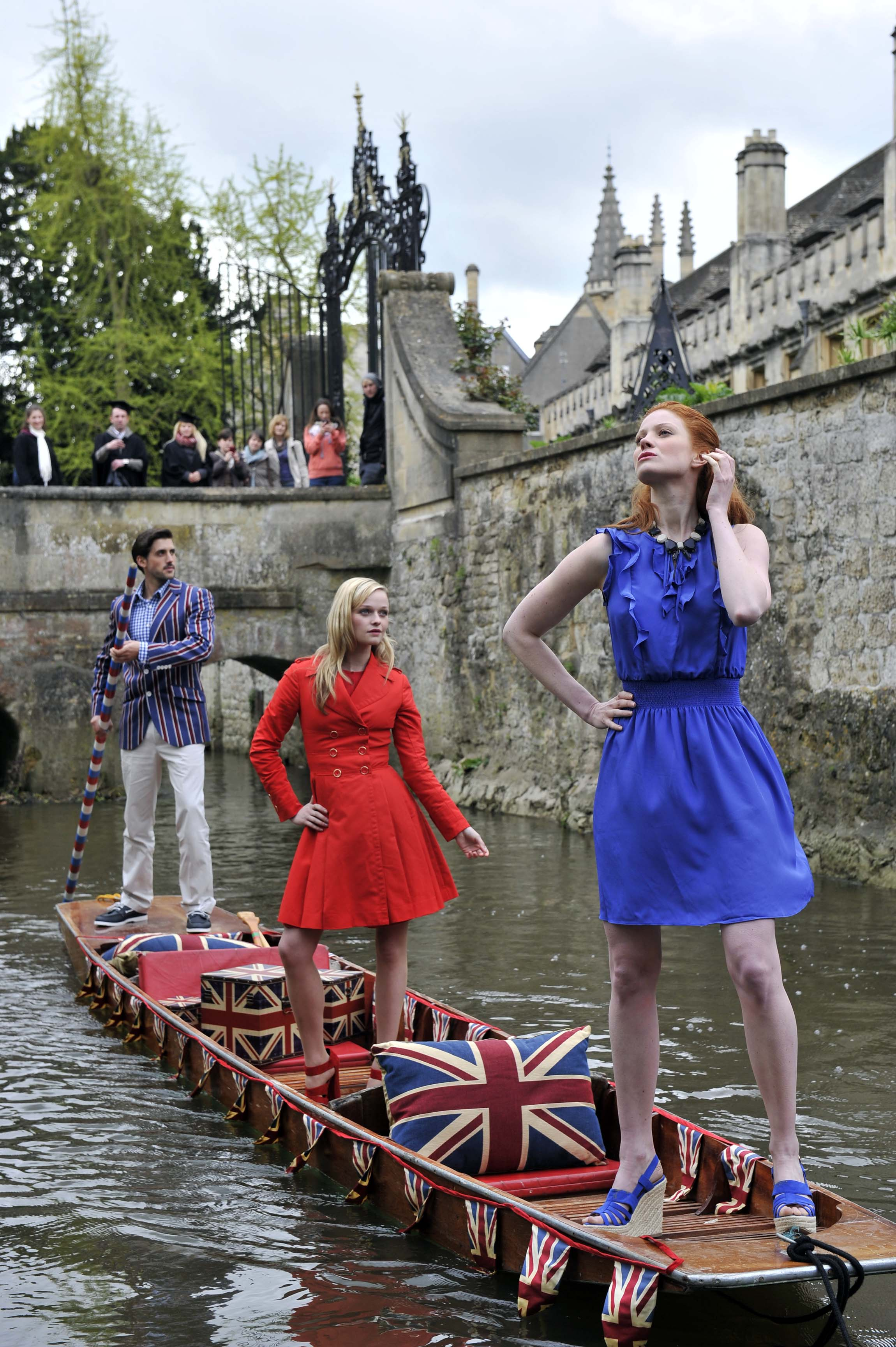 Models in designer clothes stand on a punt on a river in Oxford with people watching from a bridge