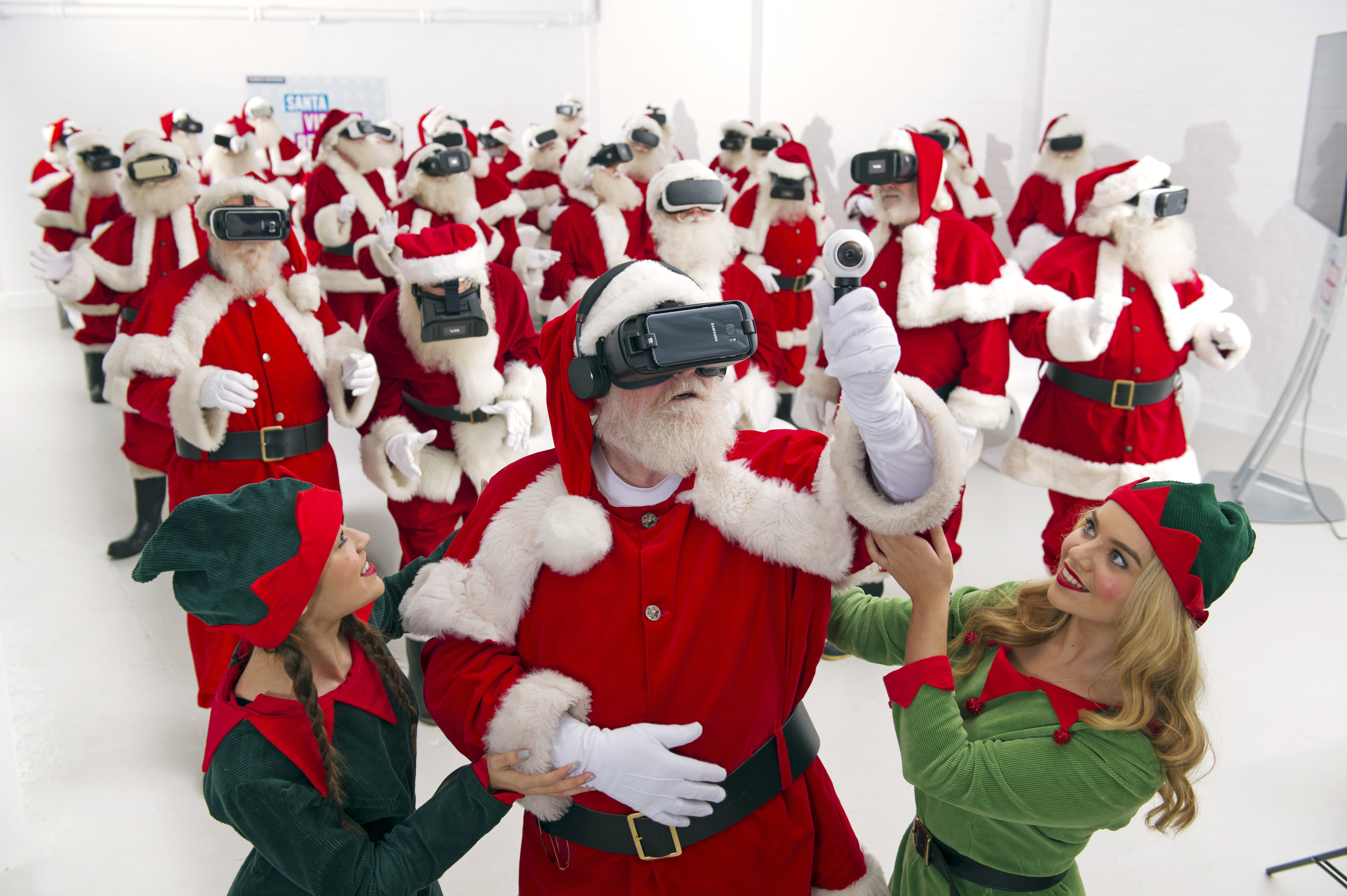 A red-suited Father Christmas wearing a virtual reality headset is guided by a pair of elves with a a group of Santas behind him.