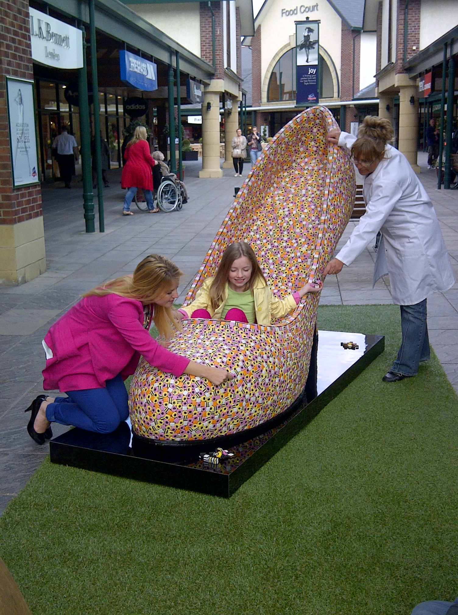 A child plays in a giant shoe made out of liqourice allsorts as shoppers watch on