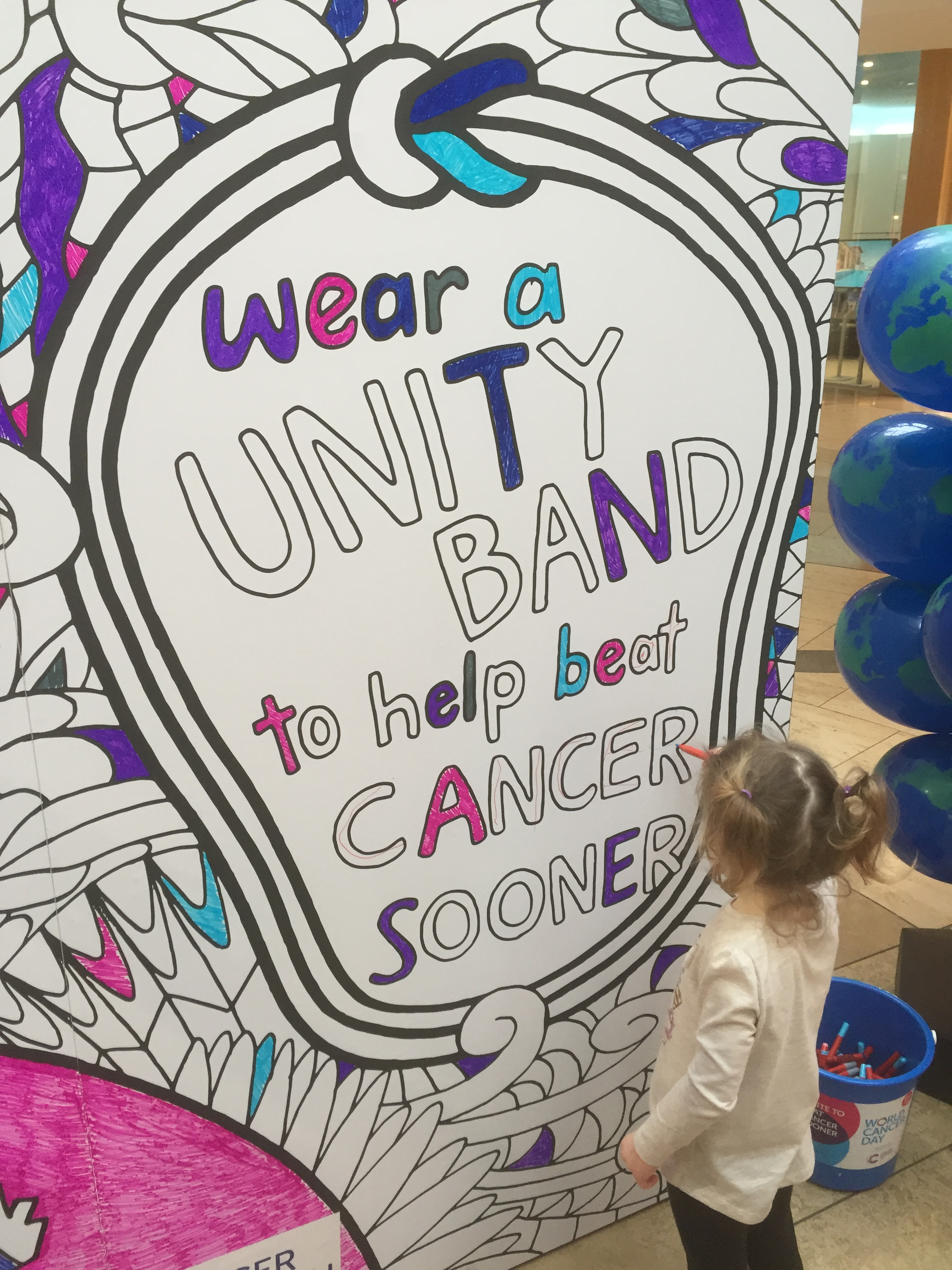 A young girl colours in a multicoloured mural for World Cancer Day in a shopping centre