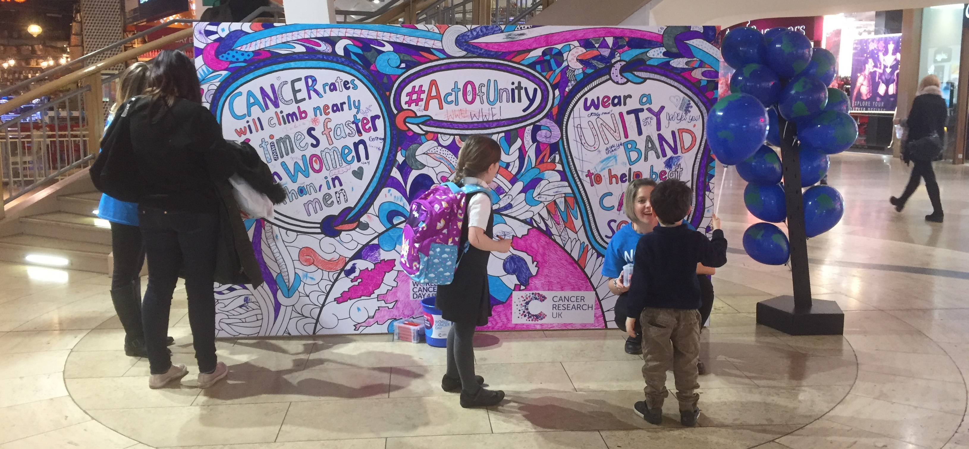People stop to interact with a multicoloured mural coloured in by the public for World Cancer Day in a shopping centre