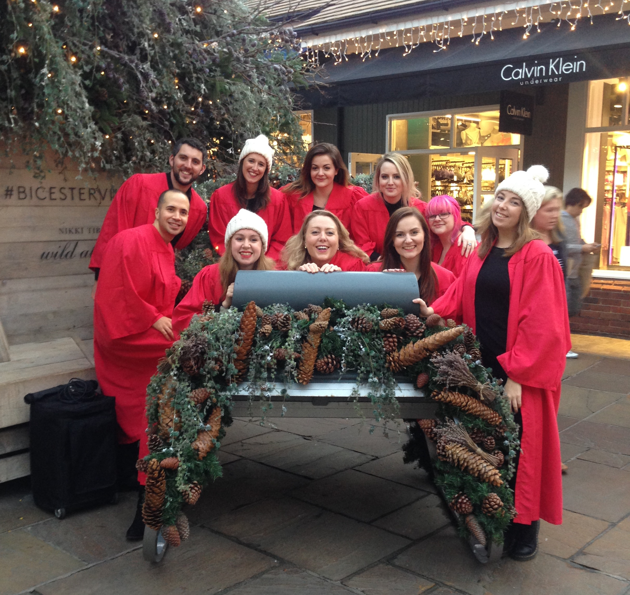 A ten-strong choir in red robes sit on a sleigh decorated in holly and pine-cones
