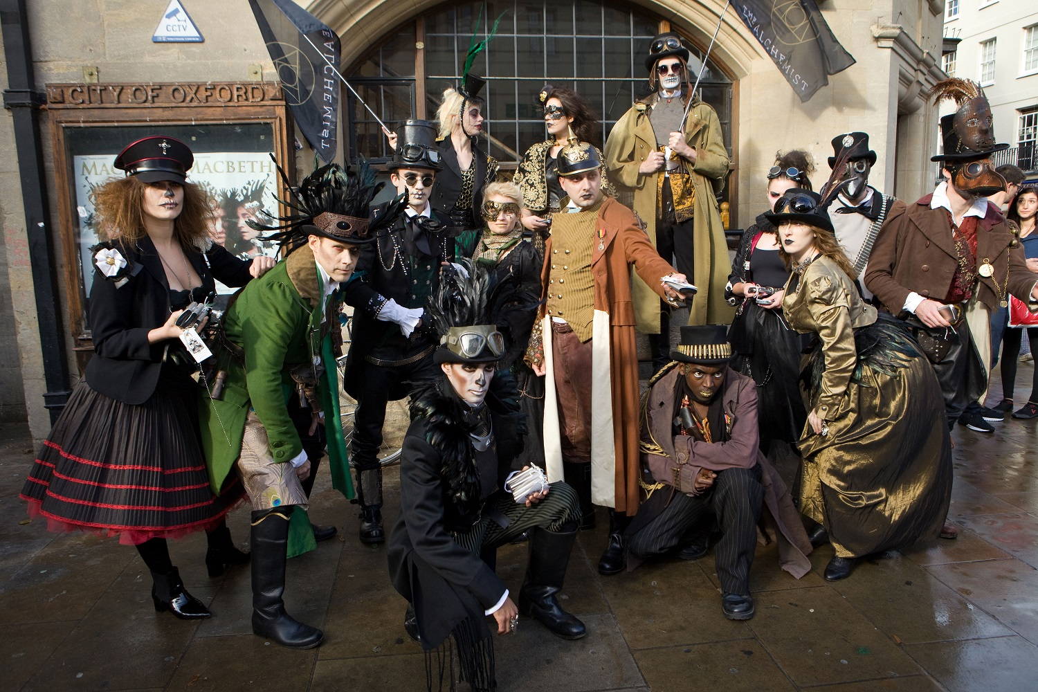 A group of attractive men and women pose outside a historic building in Oxford, wearing Streampunk clothing