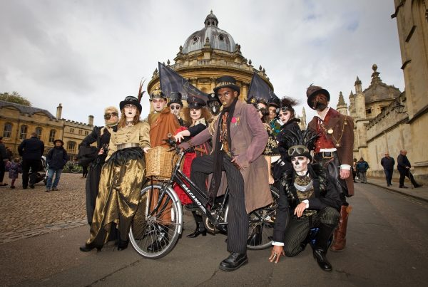 A group of attractive men and women pose outside a historic building in Oxford, one of the males straddles a bicycle