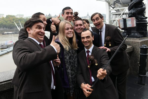 A group of men dressed as Mr Bean pose for a selfie with a girl in front of the Thames