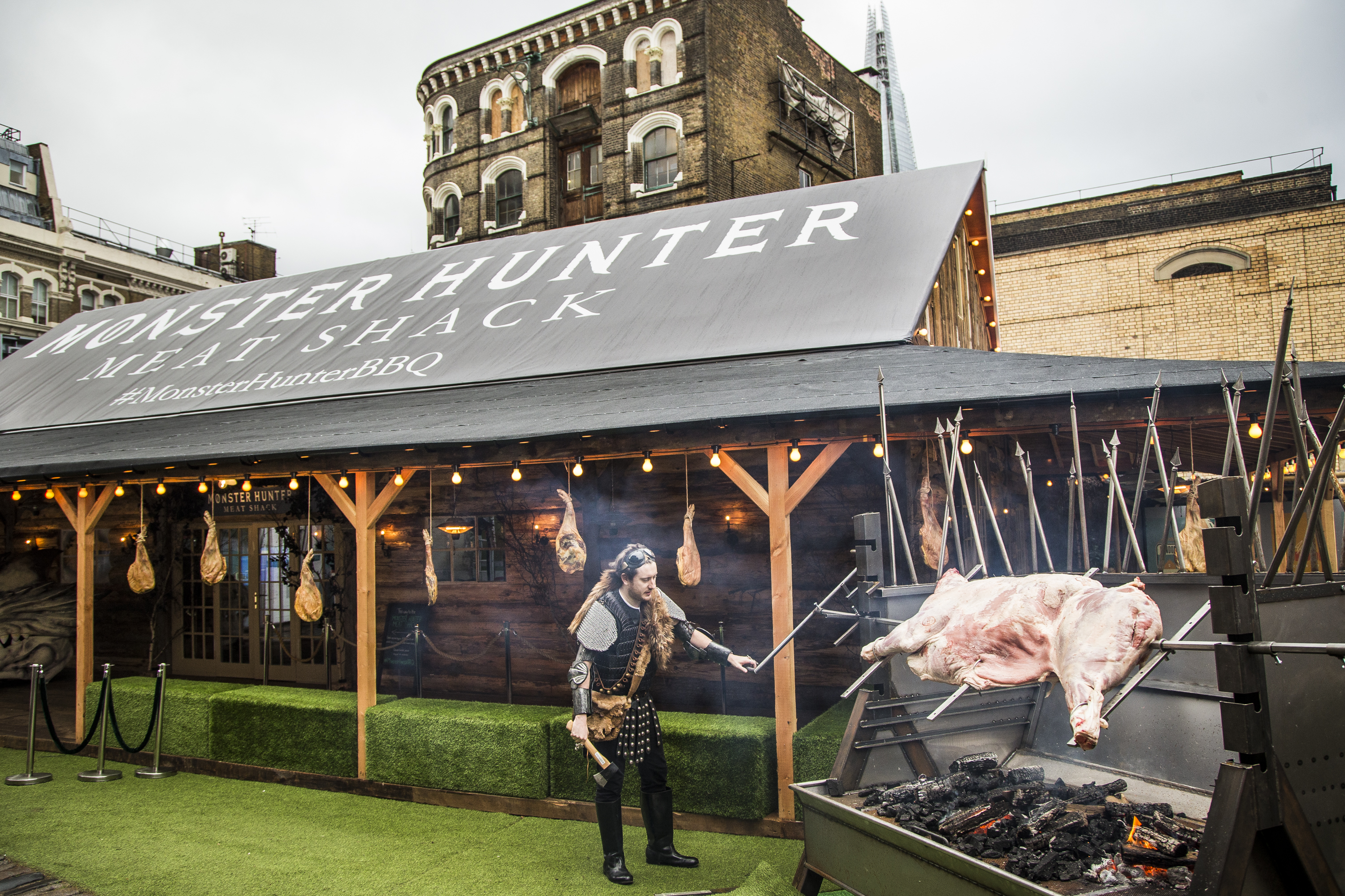 A mythical character turns a giant bespoke spitroast at the Monster Hunter Meat Shack, a restaurant pop-up in London, created to celebrate the upcoming launch of Capcom video game 'Monster Hunter: World'