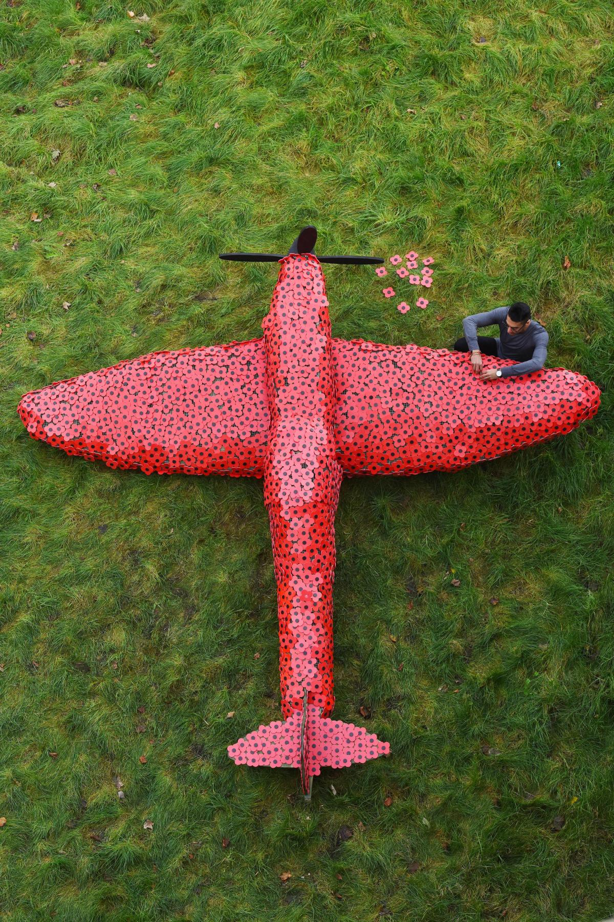 A full size spit fire installation covered in poppies for remembrance day