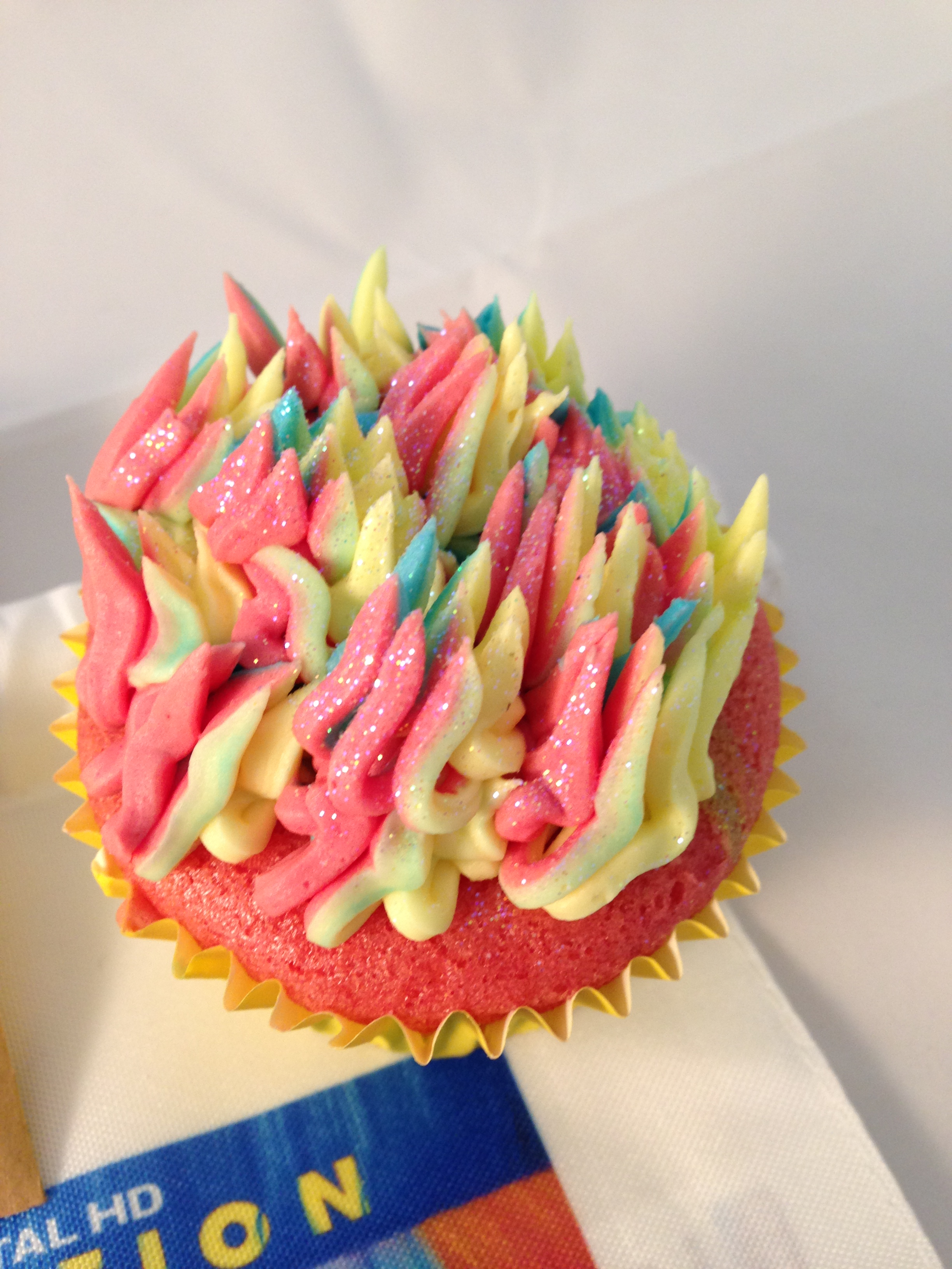 A colourful glitter cupcake, with rainbow icing whirls