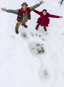 Stars Ruby Barnhill and Mark Rylance stood in a giant footprint made in the snow. They smile up at the camera in this PR Stunt at Tower Bridge in London.