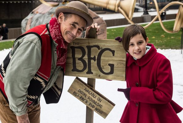 Stars Ruby Barnhill and Mark Rylance stood in front of a giant bag and dream trumpet in the snow.