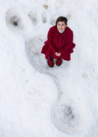 BFG star Ruby Barnhill stood in a giant footprint made in the snow. She smiles up at the camera in this PR Stunt at Tower Bridge in London.