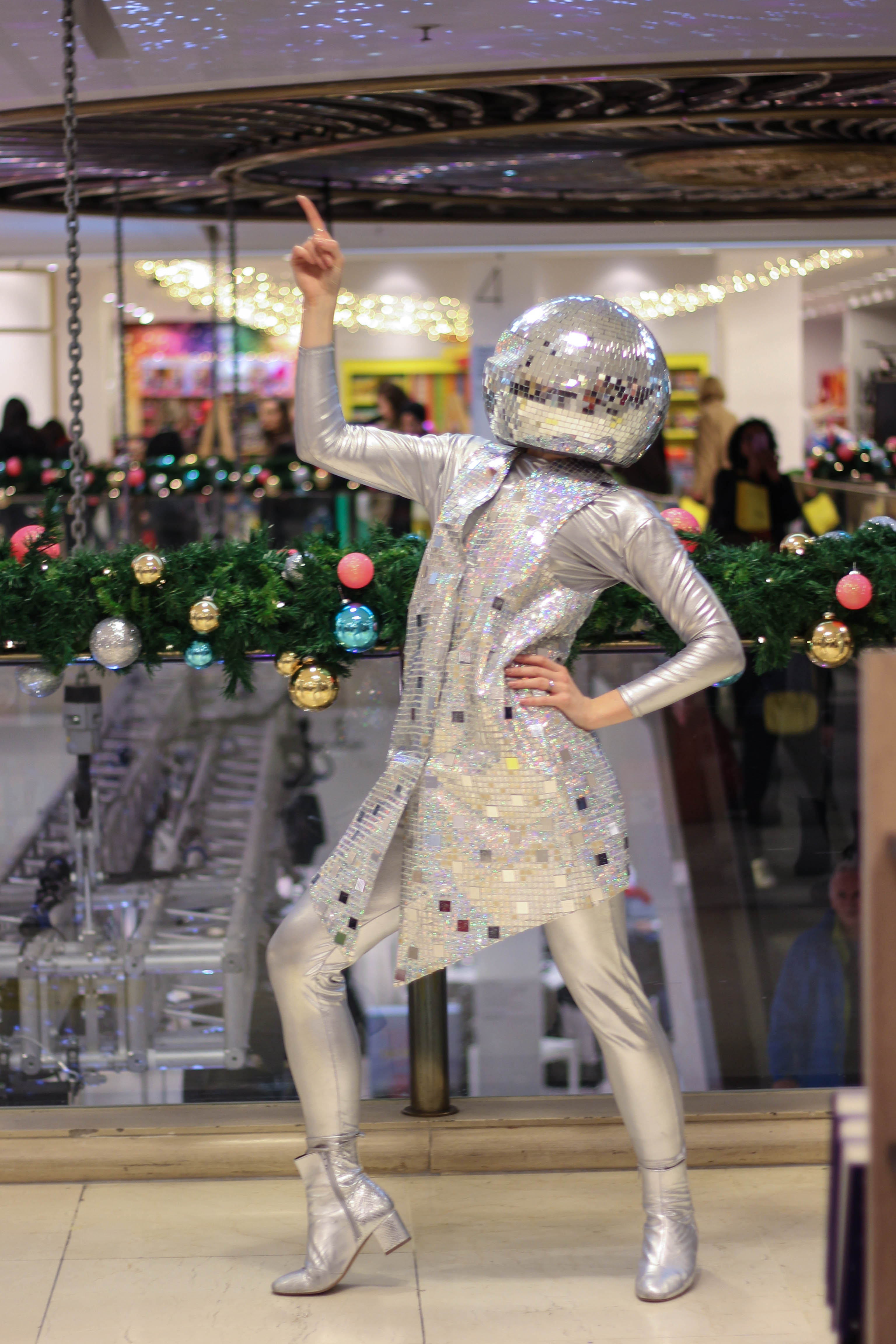 A glamorous dancer wearing bespoke silver sequin costumes with glitter ball helmets pose as part of her dance routine for Selfridges Christmas Entertainment