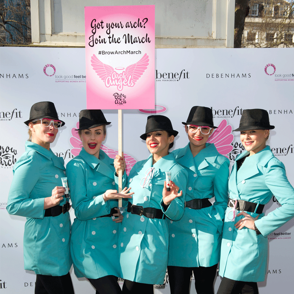 Five woman in turquiose spy outfits with glasses and black trilby hats stand infront of a branded photo wall holding a pink placard.