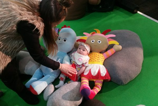A baby is placed by her mother onto comfy pebble cushions next to two colourful cuddly toy characters from In The Night Garden